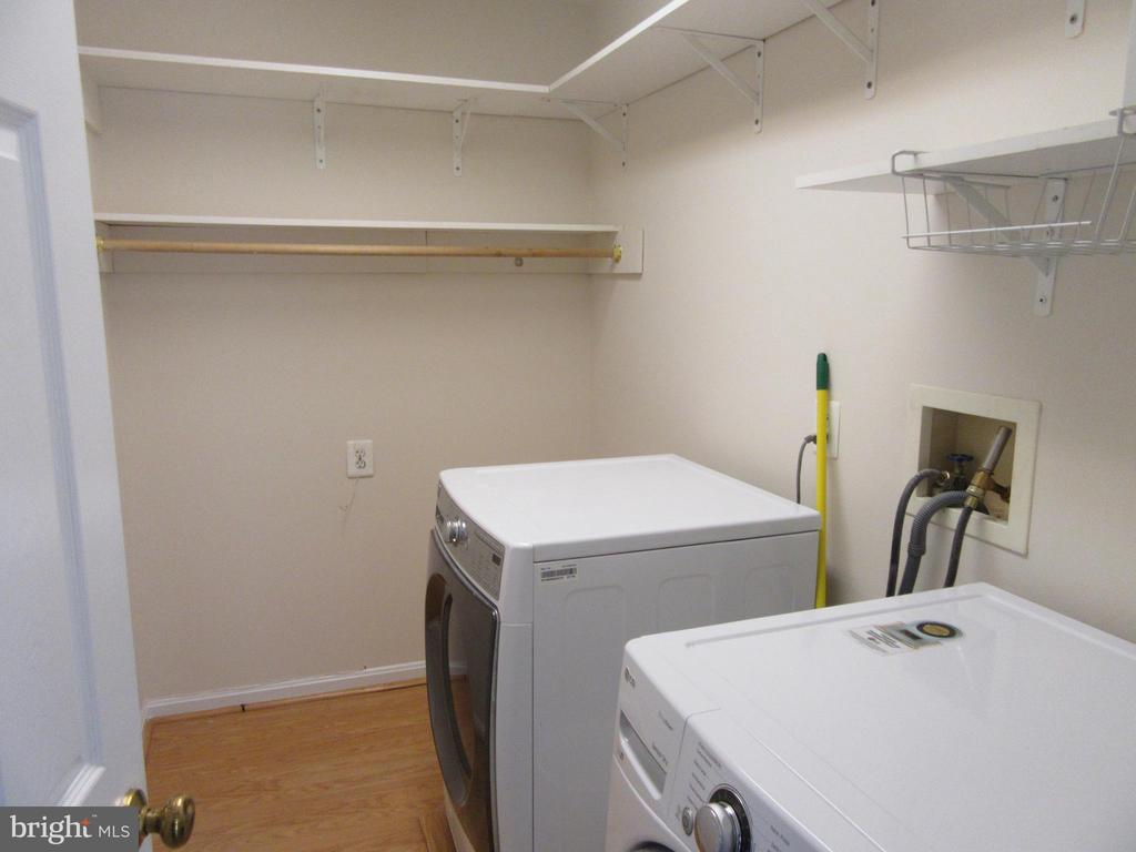 Freshly painted laundry room with shelves - 9337 S WHITT DR, MANASSAS PARK