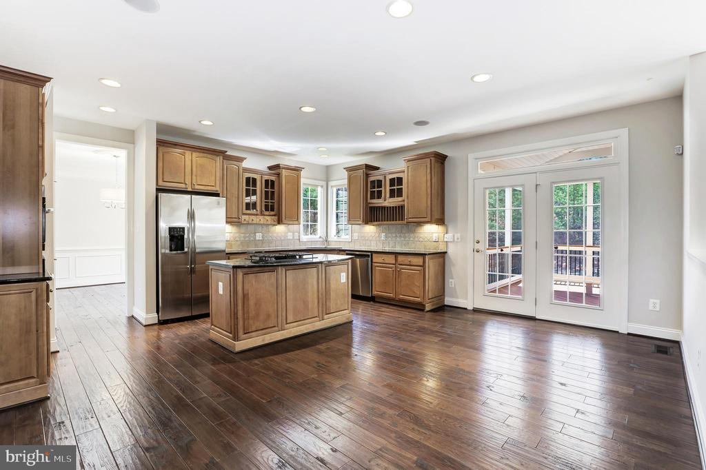 open-plan eat-in kitchen with island and bar - 43965 RIVERPOINT DR, LEESBURG