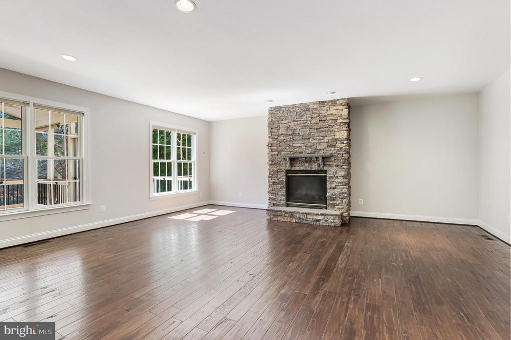 family room with floor-to ceiling stone  fireplace - 43965 RIVERPOINT DR, LEESBURG