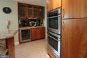 Kitchen features bar area with wine fridge - 10651 OAKTON RIDGE CT, OAKTON