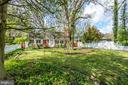Grassy front yard and mature trees providing shade - 5824 BRADLEY BLVD, BETHESDA