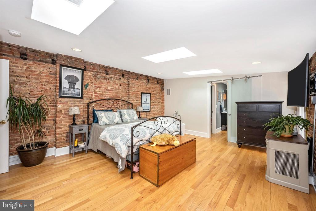 Master BR has exposed brick & balcony - 18 N WISNER ST, FREDERICK