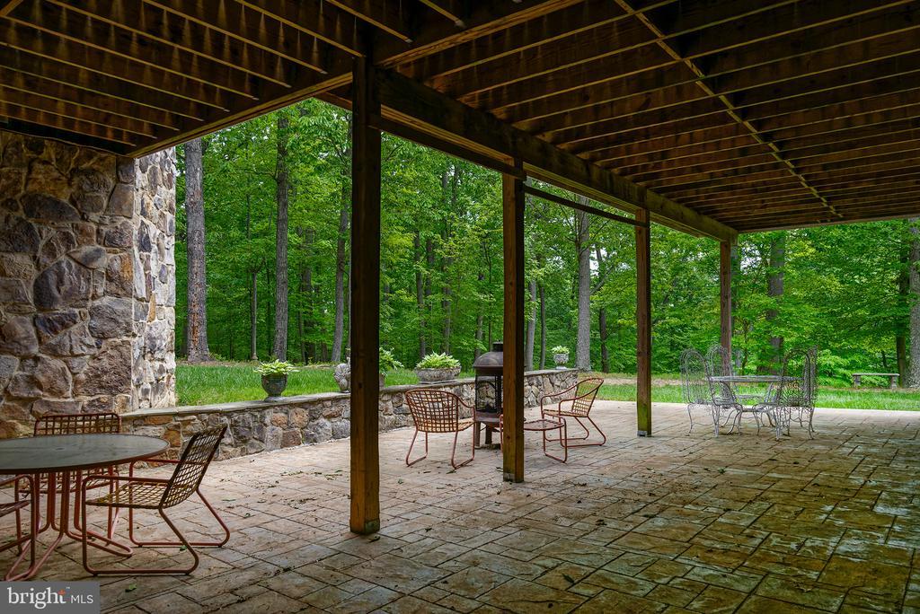 A stone patio under the mahogany deck - 41430 FOX CREEK LN, LEESBURG