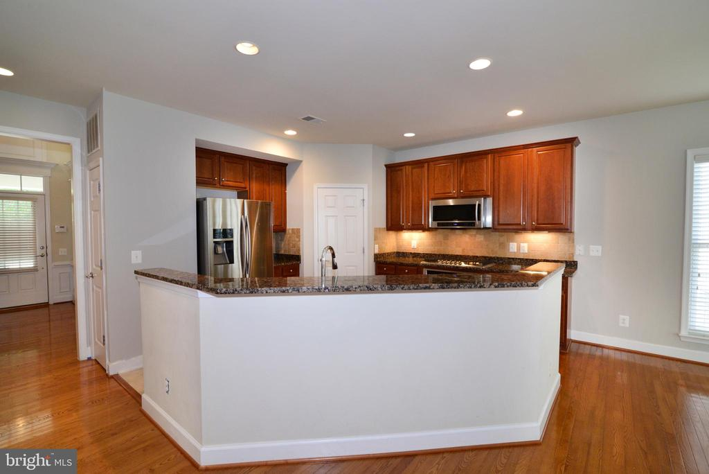 A kitchen island allows connection while cooking - 42814 RAVENGLASS DR, ASHBURN