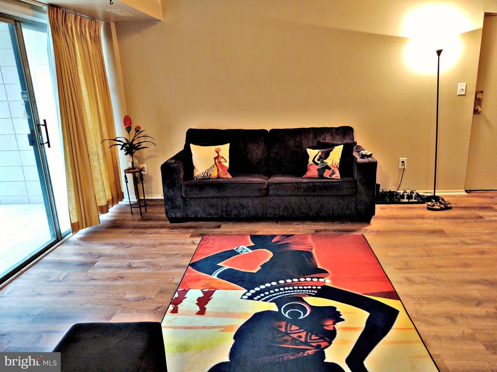 Living room with wood laminate flooring. - 7615 FONTAINEBLEAU DR #2124, NEW CARROLLTON