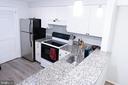 Kitchen with new floor. Washer/Dryer behind door - 1004 WARWICK CT, STERLING