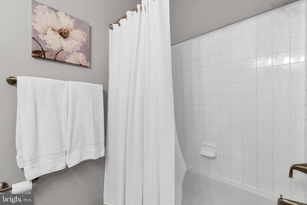 Clean & bright white tiled tub shower surround - 42509 HOLLYHOCK TER, BRAMBLETON