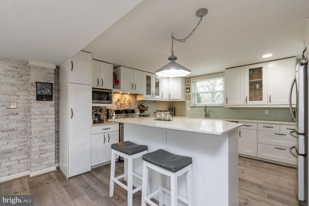 Unimposing island in kitchen with quartz continued - 1064 DALEBROOK DR, ALEXANDRIA