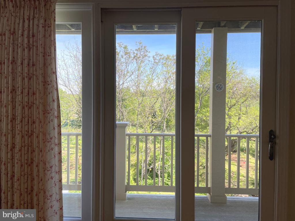 Glass doors lead to deck overlooking open space - 126 N JAY ST, MIDDLEBURG
