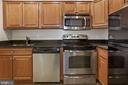 Stainless steel appliances and a granite counter. - 9761 HAGEL CIR #E, LORTON