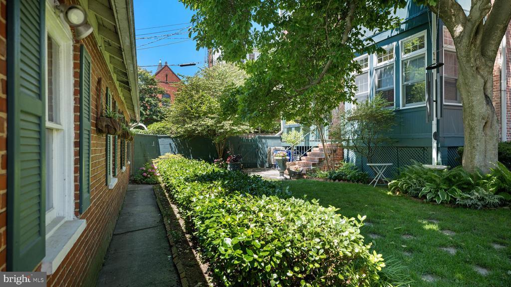 view- garage to house thru the garden - 100 E 2ND ST, FREDERICK