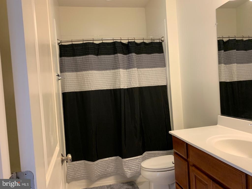 Hall bathroom with upgraded tile and cabinetry - 19383 NEWTON PASS SQ #R06V, LEESBURG