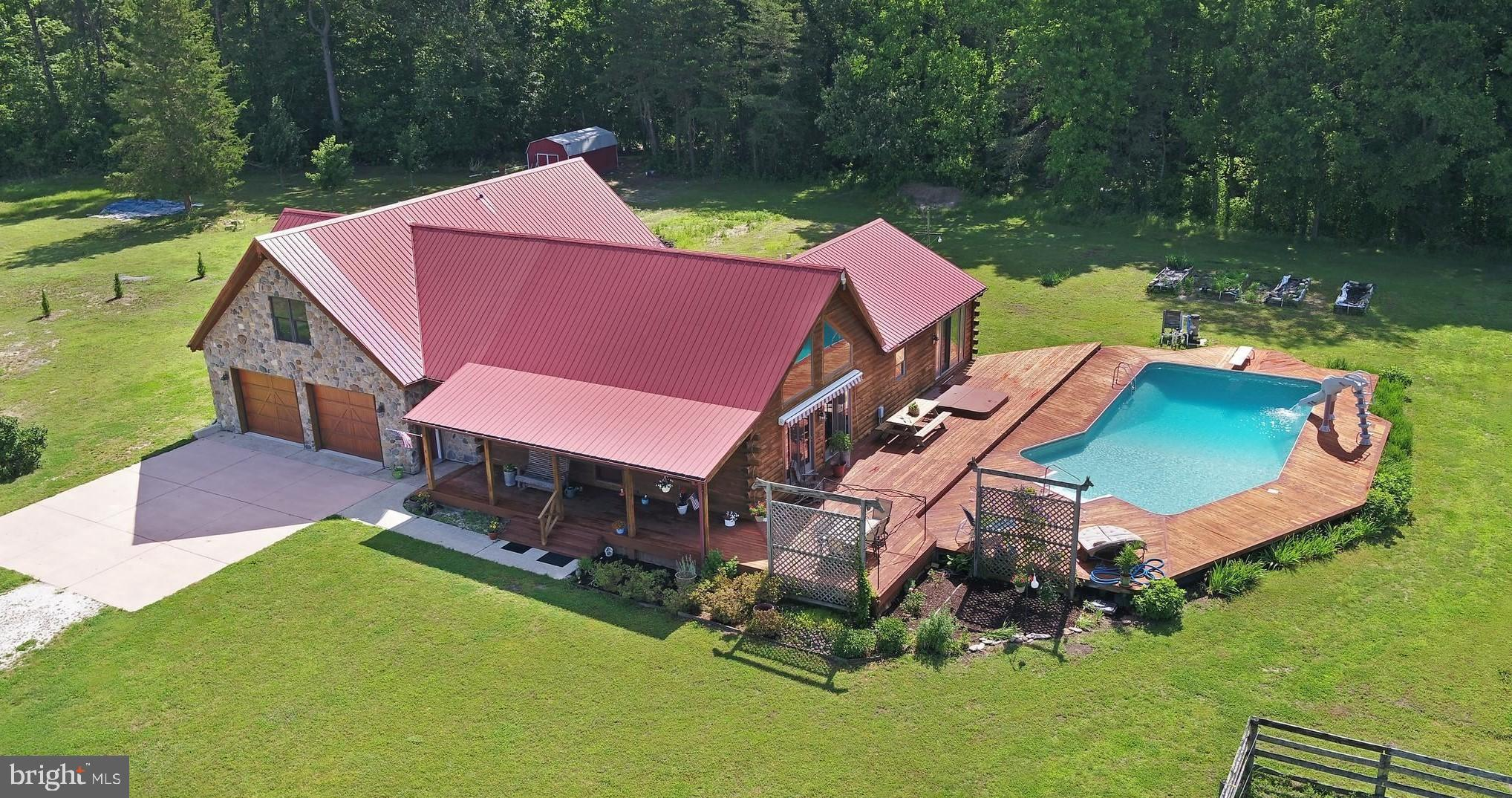 Horse lovers look no farther! This remarkable 27-acre farm boasts a custom log home surrounded by 3 fenced pastures, an impressive 40x60, 8 stall barn and an oversized equipment storage barn. Let your imagination soar in the 6-bay detached garage with electric and concrete floors. The moment you enter onto the property you will want to call it home. Pulling into to the 2-car oversized garage is the beginning of a beautiful experience. You will immediately be in awe of the rustic charm of this well-lit home with cathedral ceilings and stunning windows to watch wild turkeys and deer. A gourmet kitchen with gas stove, and granite counter tops will quickly ignite the chef in you.  The Great Room glows with a floor to ceiling fireplace and overlooking loft. Additionally, from the great room you can enjoy access to a grandiose outdoor entertaining space with inground pool and slide! And then in the colder months you can nestle up next to the wood stove adjacent to the kitchen with a good book or a good friend. The master suite and utility room, equipped with washer and dryer are suitably located on the main floor, along with a large entertaining room and/or additional living space. Bonus: the area above the garage is partially finished, including electric, plumbing, HVAC, and finishing materials--offering nearly 1000 more sf of living space. If that is not enough, this property also has access to Redden Forest for your leisure days on the trails.  Conveniently located near the beach and easy commute to the surrounding major cities makes this property a must have.