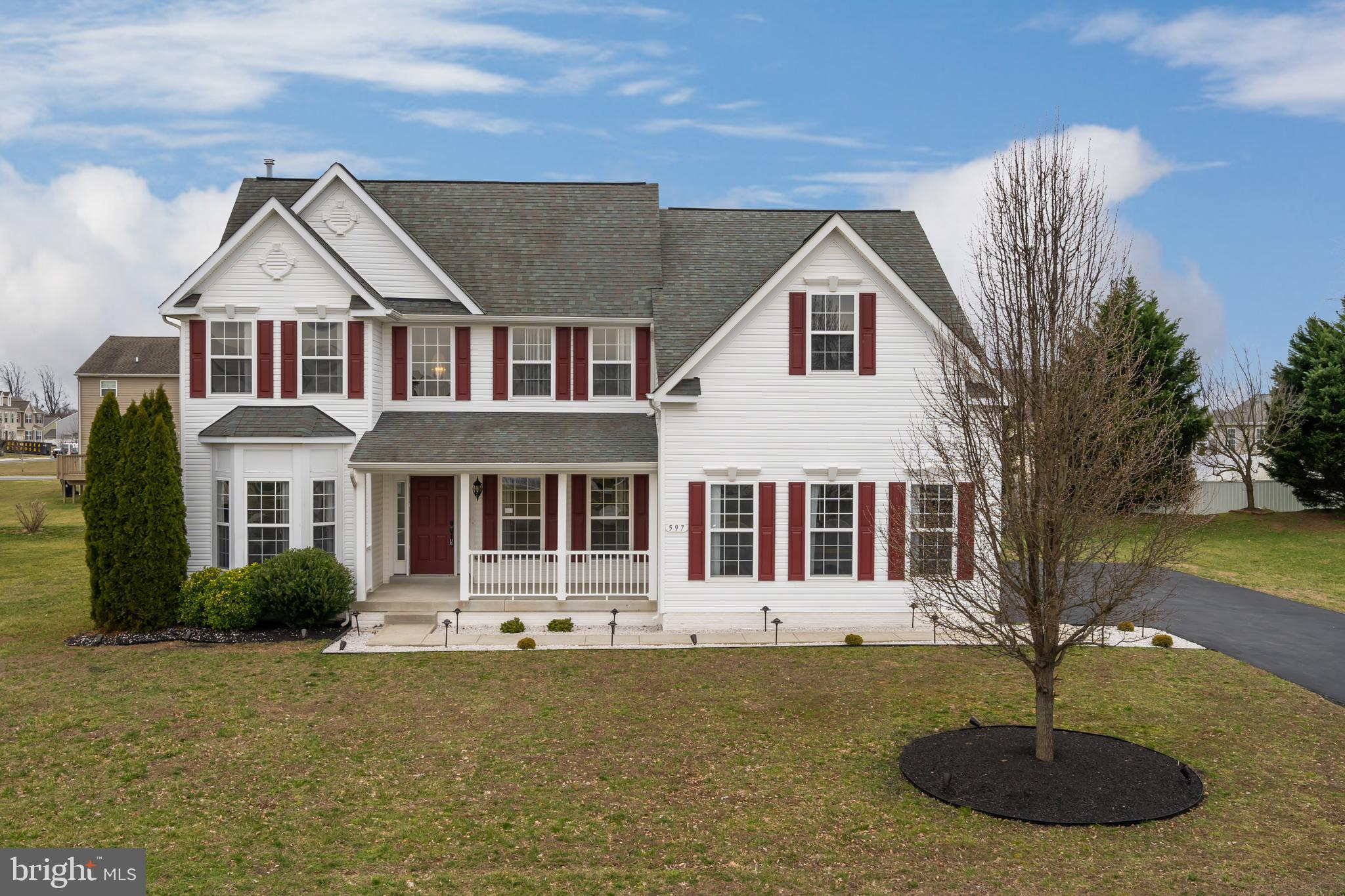 Magnificent home in Magnolia! Just 5 mins. off Rt. 1 and nearby to Scotton Landing boating access area and DAFB, yet tucked in peaceful alcove of countryside, this grand white siding/red shutter 2-story 5BRs/4 ~ bath home is one of few in community that touts this dramatic exterior. 1st glance leaves lasting impression! Turned 2-car garage keeps front clean-lined, while clusters of shrubs/evergreens sit to one side of home and ornamental tree on other side. Large white-railed porch decorates front. 2-story foyer sets stage for on-trend, on-point home! Contemporary edge, dramatic architectural elements and open floor plan offers modern, sought-after style home. Wide-plank cherry hardwoods contrast dramatically with cloud gray paint throughout. 2nd-level window highlights brass chandelier, crown molding and balcony overlook. To left is flex space with beautiful walk-in bay window; make it formal LR, 1st-floor office or retreat room. Opposite and through oversized entrance is DR with matching crown molding and chair rail. Plenty of space for intimate dinner parties or large dining events! Hall that leads back to main space consists of DD closet, PR with continued hardwoods, modern-edged cherry vanity that coordinates beautifully with floors, and access to LL. Plush carpeted steps lead down to pillared bottom floor that is amazing, finished and full footprint of home. Light polished hardwoods appear here and pillars are repeated throughout expansive room, creating continuity. Truly extra, entertaining square footage! Main space is huge as great game/rec room. Edging perimeter of main space are pocket rooms including full bath with shower and black vanity, angled DD BR with DD slider closet, work-area with cabinets, computer room/play room, huge under-the-steps closet and outside door to backyard. Simply smart space! Back of home on main level boasts vaulted-ceiling great room with stunning floor-to-ceiling chunky jutted gray/charcoal stone FP with polished ceramic tile 