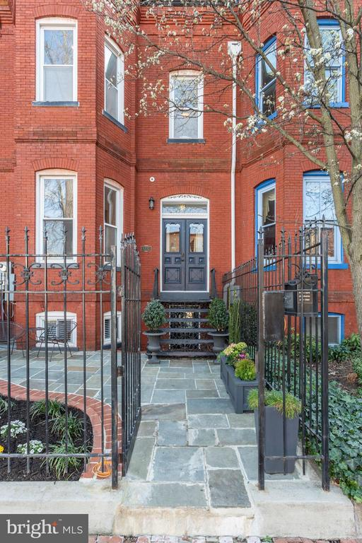 Gorgeous late 1800's residence filled with character and period details in coveted Logan Circle (including bay windows on all levels and 5 working fireplaces). This home's full and recent renovation defines the desirable meld of classic architecture with urban modern luxury, including green Super smart technology conveniences and surround sound systems. Its main level features 11-foot + ceilings, living room, dining room and a gourmet kitchen each with wood-burning fireplaces. Upstairs boasts a master bedroom with fireplace, custom built-ins and en-suite bath, two additional bedrooms (one with fireplace) and a hall bath with claw-foot tub. The lower level, with legal C of O offers 2 bedrooms, 1 bath and kitchen, enjoys exposed brick walls and its own w/d's - AirBnB rental income on average is $5K per month! Striking details include hardwood floors throughout, exposed brick walls, dental crown molding and period mantles. Secure parking for 2 cars, with electric car charging power hookup and roof beams for solar panels complete this fantastic offering! 14th Street corridor at end of the block, U Street and Shaw offerings close by, too. Walk Score 98, Transit Score 100, Bike Score 92.