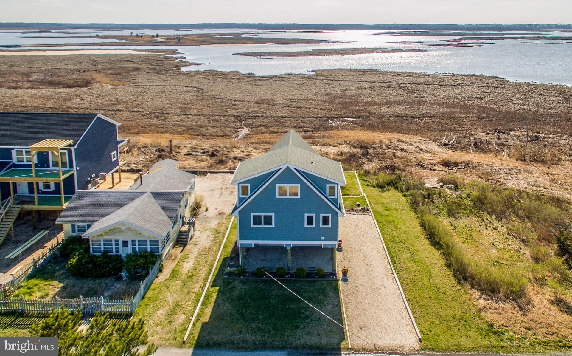 A Little Slice of Heaven! This Pristine home located with stunning views of the Prime Hook Wildlife Refuge allows for tranquil days on the private beach directly across the street to enjoy hours on the calm waters of the Delaware Bay. Just entering this sun filled open floorplan home will amaze you with the  living area that features a beautiful tongue and groove ceiling, huge granite island for entertaining, gas fireplace and the large rear deck of this property allows for privacy and the most spectacular sunsets.  Large windows throughout overlooking the Refuge allows for an expansive view to catch the amazing osprey, marsh hawks or barn swallows flying into your view with even a view over the kitchen sink! A master bedroom is on the same floor as the living area with full bath and wall mounted TV. Grand cathedral ceiling opens to upper loft/living area and bedroom with its own full bath, split HVAC system to fine tune temperature. Great views of the Delaware Bay from this level as well. Last but not least this property features a brand new outdoor shower an abundance of storage under home for your beach equipment, Kayaks, and more. THIS IS A MUST SEE!!! Schedule your appointment today!