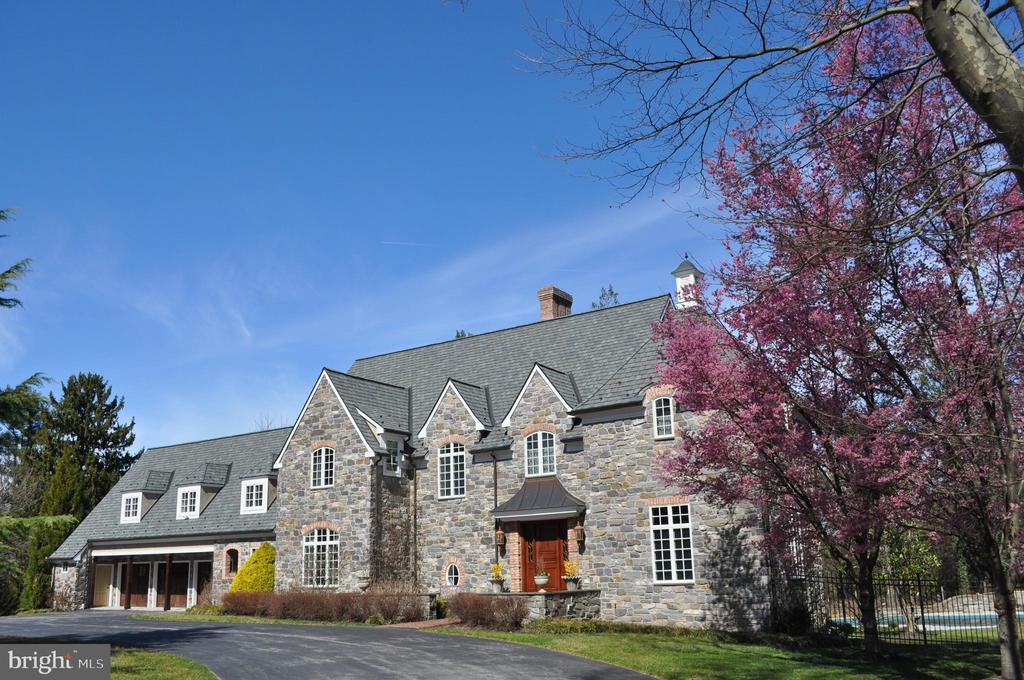 Virtual tour: https://mls.homejab.com/property/view/1001-north-ln-gladwyne-pa-19035-usa A magnificent, custom-built 13-year old French country style home featuring 4-sides of stone with all the right modern touches on a corner lot in Gladwyne, an absolute once in a lifetime home. This home was designed by renowned architect, Fred Bissinger, and presents a stately and dignified curbside presentation, a 3-car attached garage, an absolutely stunning exterior entrance, with a large, ivy-laden stone patio and a beautiful cherry wood door. The home features classic discreet rooms, modern open concepts, with finished hardwood floors imported from Belize and recessed lighting throughout. Upon entering, the foyer, accented with a natural stone floor, introduces a grand layout with direct access to the living room, which provides a direct line of sight to the backyard of the property, and features white molded recessed shelves and a huge hand crafted stone mantel fireplace. Immediately adjacent to the right of the entrance is an elegant half bath with granite sink, a classic office or study with windows on three walls and built-in shelves. Down the hallway from the entrance, heading towards the rear of the home and passing the main stairwell, there is a large family room, with another beautiful fireplace which offers direct access to a covered veranda and an extra-large brick paver deck overlooking a private salt water pool with a travertine deck, pergola, firepit and a brick accent wall. The family room opens up, unimpeded to this home's gorgeous, gourmet kitchen inclusive of beautiful granite counters, a custom built stone range hood with a tiled range backsplash, custom cabinet faced refrigerator, an extra-large granite island (that can seat four and has its own sink), and a suite of modern, stainless steel appliances. The breakfast room adjacent to the kitchen is the homey and comfortable space you crave for day to day meals. The elegant dining room across from the family room is well suited for intimate special evenings and offers direct access to a butler pantry with backlit glass doors accenting the custom cabinetry. The main floor of this amazing space also offers a convenient rear mudroom and an adjacent half bath with a soapstone sink. Specialized architectural features include stylish wood paneling throughout and varying ceiling designs in virtually every ground floor room. Up the stately iron-railed staircase, the second floor features five spacious bedrooms accessed by a connecting hallway accented with paneled walls and recessed lighting. The master suite is gorgeous, with a massive walk-in closet that flows from the en suite bathroom complete with a luxurious walk-in shower featuring a steam unit, a soaking tub, a double sink vanity and heated floors. Two additional bedrooms have en suite baths, and another two bedrooms share a full bath with separate sinks. The extra-large bedroom at the opposite side of the house from the master suite offers the opportunity to create a second master bedroom suite for in-laws or grown children and features vaulted ceilings and a dedicated full bath. The basement offers another large finished space, a perfect media room, spacious rec room, gym space, laundry (in addition to a laundry upstairs), and full bath. Living at 1001 North Lane, you will be one short block from the famous Philadelphia Country Club as well as in close proximity to numerous public Gladwyne parks, access to I-76 and greater Philadelphia will be only moments away, and bustling Conshohocken with all its amenities will be in your neighborhood. This is a gorgeous, absolutely fantastic custom built home you are sure to fall in love with. Schedule an appointment today!