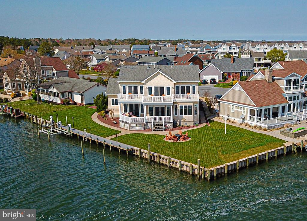 Beautiful Bay Front point lot with panoramic views of the Ocean City Skyline & Manklin Creek! This gorgeous home features hardwood floors throughout, a spacious Foyer w/shiplap accent wall & 2 coat closets, an office w/built in shelving & plantation shutters. The updated Kitchen has granite counter tops, SS Apps. w/center island,  dining area w/a beautiful rectangular light fixture & plantation shutters. Relax in the cozy Sunroom located off the dining area w/awesome views of the water. The LR has built in shelving, a two sided gas FP,  access to the rear deck & hot tub. The MBR has an attractive shiplap accent wall, gas FP & access to the rear deck & hot tub. The En-suite has two(his/hers) bathrooms w/a shared tiled walk in shower,  Jacuzzi tub & his & hers walk in closets. The first floor includes a powder room & laundry room w/a built in ironing board w/cabinets. The second floor features a 2nd MBR w/walkin closet. Two other BR's share a Jack & Jill bathroom. All 3 BR's have access to a common balcony w/priceless views of the sunrise & sunsets. There is a bonus room located over the garage & a huge walk in storage closet. 150ft. of new vinyl bulkhead in 2019 w/2 boat slips including a boat lift w/new maint. free dock & jet ski lift. The back yard has recently been landscaped w/pavers, new sod, plantings & irrigation system.  This is a Must See in Ocean Pines!