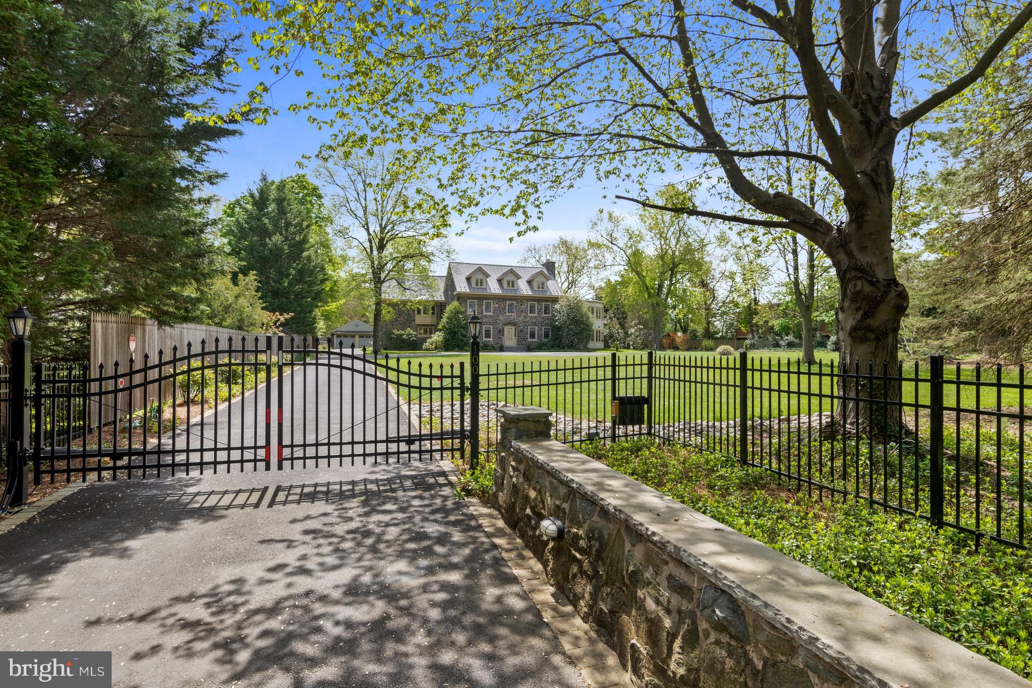 An Oasis in the Heart of Greenville. Enter the gates at 100 Buck Road and feel the cares of the world slide off your shoulders as you arrive at a 1.8-acre park-like estate that is steeped in history, impeccably maintained, and equipped for an active 21st century owner. Built in 1918 from granite, 100 Buck Road has most recently been the happy home of a multigenerational family, who enjoyed large-scale entertaining on a fabulous covered terrace with a TV and firepit. Picture the family  playing hide and seek throughout the house, practicing soccer in the yard, and gathering in the big, welcoming kitchen. It's a truly unique place that is peaceful, private—and just a short stroll to Greenville's shops and restaurants. The property is an ideal location for professionals who could work from their very own oval office overlooking the verdant grounds, a spacious semi-circular sunroom equipped with audio-visual equipment. Zip around the grounds by golf cart and enjoy birdwatching, gardening, or working in a dedicated professional-style woodshop. With parking for 16 vehicles, the property is zoned for an owner-occupied business, including a bed-and-breakfast inn.  A stunning second-floor library features wood paneling and a secret door. Modern owners will appreciate more than $1 million in renovations, including zoned heating and cooling, updated windows and standing-seam metal roof.