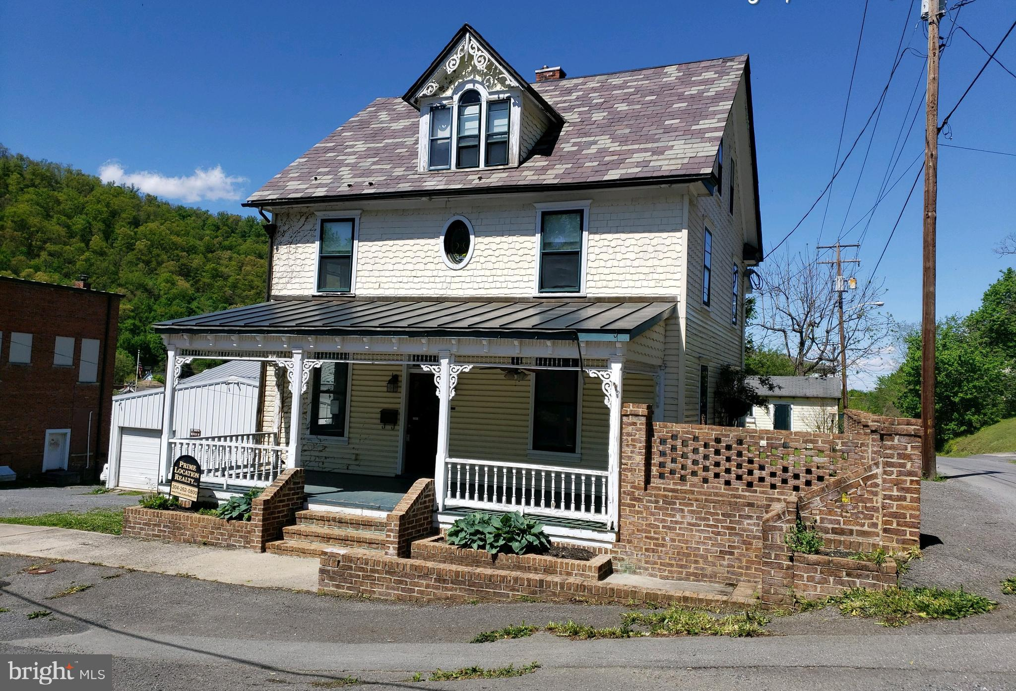Close to downtown, colonial style home boasts of potential. With 5 BRs, 5 full BAs, a full basement and outbuilding for storage, fenced rear yard, covered porches and small apartment type setting in attic with a kitchenette and separate laundry area, home could be perfect for entertaining.
