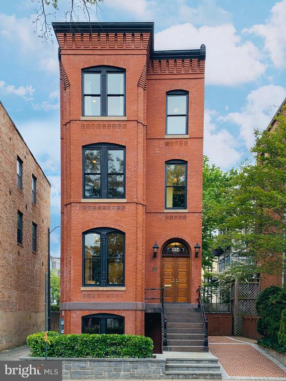 """An architectural gem - This unique and exquisitely renovated stand-alone rowhouse sits in the heart of Logan Circle.  Built in 1892, the recently-repointed brick home exudes character, from gas lamps, stunning wood double front door with stained glass transom, patio, and brick driveway on the outside to soaring ceilings, bay windows, original hardwood floors, 2 fireplaces, gourmet kitchen with high-end appliances, and new custom wood windows throughout.  The house includes a completely separate and beautifully renovated garden-level apartment that has 1 Bedroom, 1 Full Bath, kitchen with gas stove and granite countertops, laundry, gas fireplace, and large bay window that fills the living room with natural light.  Across the street from trendy Milk Bar and Vida Fitness, and right around the corner from Whole Foods Market and Starbucks, as well as a plethora of dining options along the 14th Street Corridor - one block away. Virtual brochure, floor plans, and disclosures available in """"Documents."""""""