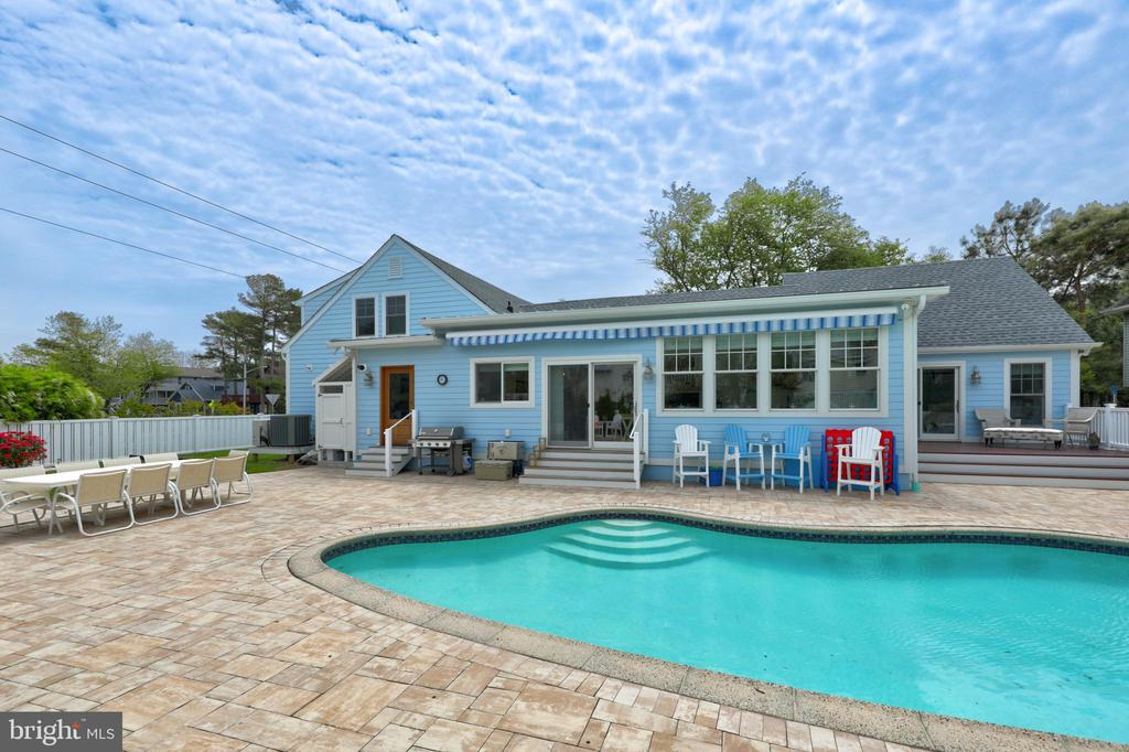 Simply stunning fully renovated home located on a spacious double lot with an in-ground pool and only 2 blocks to the beach! Voted #1 on the cottage tour in 2018, this 6 bedroom, 4 bath home has been beautifully updated while still honoring the classic coastal cottage style and architecture and incorporating timeless modern luxuries. Notable features include a double sided fireplace, granite countertops, tiled backsplash, wainscoting, exposed wood beam ceiling, beautiful hardwood flooring throughout and so much more. Featuring an open floorplan with an additional family room, 3 en-suite bedrooms, two on the 1st floor and another on the upper level, a charming screened porch and expansive hardscaped patio around the pool with Travertine stone (keeps cool in the sun), there is plenty of space to entertain guests both indoors and out. Enjoy the best of both worlds with your own private oasis and pool, while being just a short walk to downtown Bethany and the beach. This home is sold furnished and is ready to be enjoyed!
