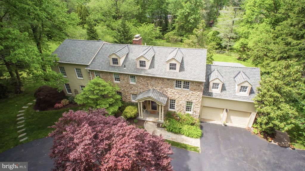 This impressive stone, center hall Colonial is unparalleled in both its interior and exterior detail. It is situated upon park-like grounds on close to an acrein the heart of Bryn Mawr. This 4 bedroom, 3.2 bath home offers a 1,200 sq ft addition that upgrades the space to include a master suite, main level study and a supplemental basement finished into extra living space. You will admire the many details including the hardwood floors, 5 fireplaces (4 gas) architecturally appealing custom mouldings and built-ins, and STUNNING light-filled views from every window. The main level library provides comfort and convenience with a gas fireplace and a granite topped wet bar with custom cherry cabinets. For the work at home professional, this home has a Minor Home Occupation Certificate of Occupancy with separate entrance .The Kitchen has an abundance of prep and storage space with WoodMode custom cabinetry, JenAir downdraft cook top stove, double GE Profile ovens with convection, microwave, Bosch dishwasher and an adjacent fireside Breakfast Room and mud room. The generously sized formal Living and Dining rooms provide dramatic entertaining spaces. Upstairs you will find an exceptional Master Bedroom featuring a cathedral ceiling, fireplace, sitting room with granite topped wet bar, Master bath with custom double bowl vanity, jetted soaking tub, large stall shower with rain head and bench and a walk-in closet with custom organizer. The Prince/Princess/Au Pair Suite features a private bath and sitting room. The two additional large bedrooms which share an updated bath both offer ample closet space. In the daylight, walkout Lower Level you will find lots of additional living space including an exercise room and recreation area with fireplace and a powder room. The lower level walks out to a wide rear terrace with prolific natural views of the fenced landscaped grounds. This property provides a 2 zone HVAC system, new 75 gallon hot water heater, walk up floored attic with att