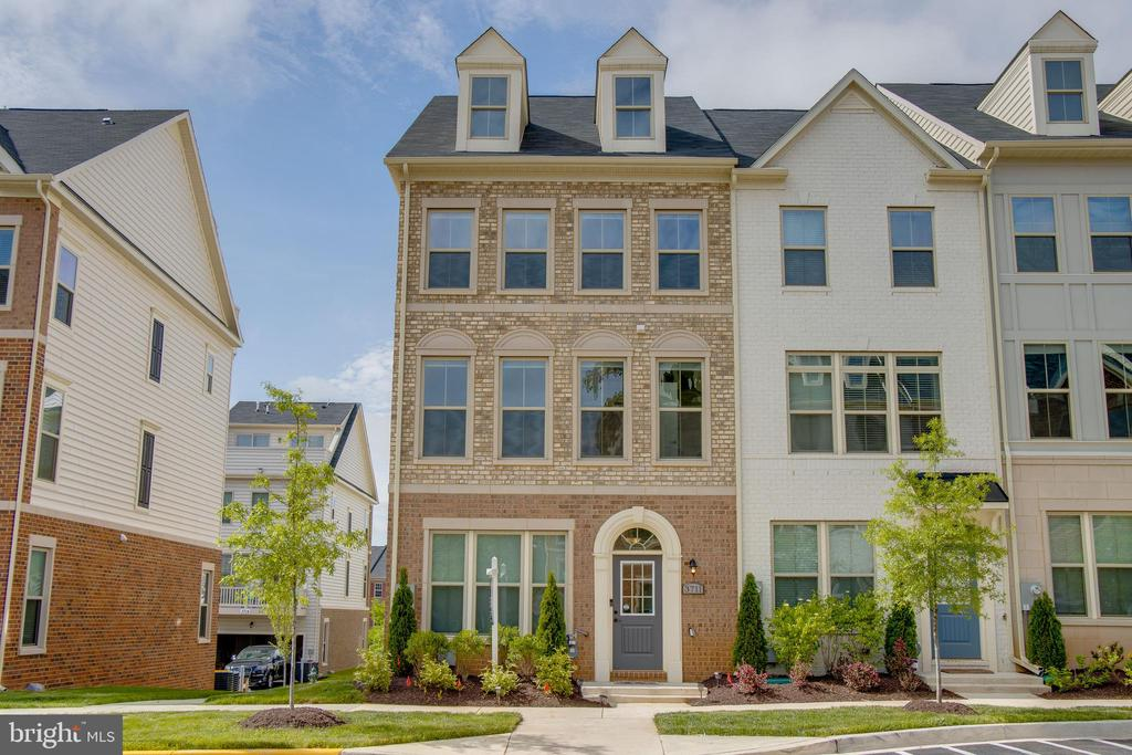 This beautiful, light filled townhome boasts 4 finished levels, 4 bedrooms, 4.5 bathrooms, plus convenient city living in the desirable Reserves at Dakota Crossing community in Fort Lincoln. Home was built in 2018 so everything is new! The first level features a bedroom and full bath with 2 car garage. The second level features modern, open floor plan with hardwood floors and a kitchen that flows into living space. There is also a half bath so the space is ideal for entertaining. Kitchen features upgraded appliances~throughout plus custom lighting on top of the kitchen island. The home's third level features~the master suite with spacious master bath and closet, plus an additional 2 bedrooms, ~full bath, and laundry. The washer and dryer were purchased in November 2018. The fourth level boasts hardwood flooring and consists of a den (or 5th bedroom depending on your preference), a full bath, and a beautiful and spacious terrace that looks out onto the community~and is perfect for grilling and enjoying spring and fall weather. The home has ceiling fans in first level bedroom, second floor living space, and master suite. It also features room darkening blinds throughout. Home is walking distance to the Shops at Dakota Crossing, which has a Lowe's Home Improvement, Costco, Chick-fil-A, Marshalls, Starbucks, Chipotle, and much more. If you want a new home with new appliances and easy access to city living without compromising on space--this is it!~