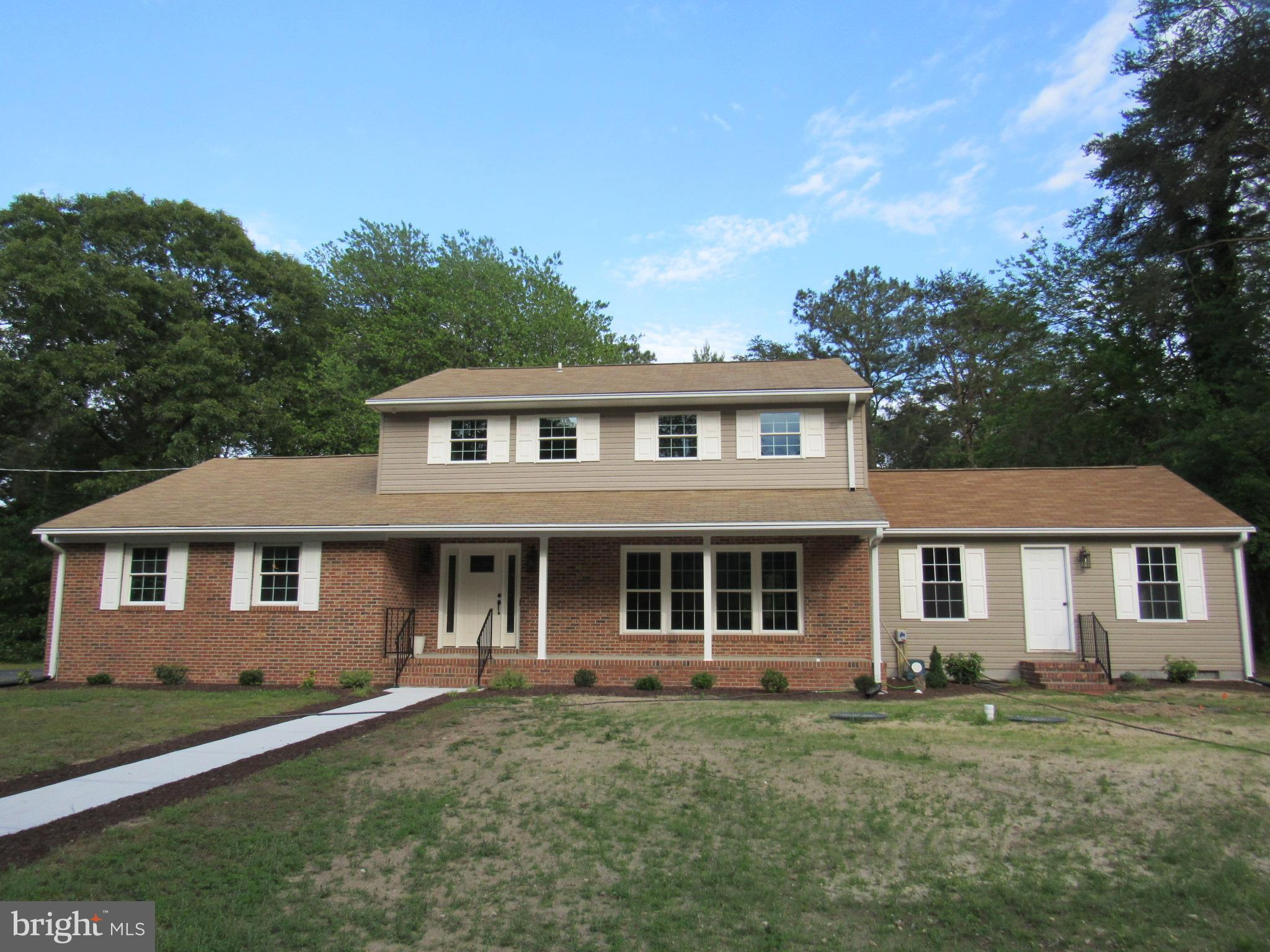 """Make this amazing home yours! This 5-BR, 3.5-BA Brick Front Colonial is New New New from one end to the other! This 2,639 sq ft home with 2-car attached garage and front porch offers a maintenance-free exterior.  This home is BETTER than new and features a wonderful first-floor IN-LAW SUITE.  The In-law suite offers a Kitchenette (10' x 8'6""""), Combined Living/Dining area (13' x 12'), Bedroom (10' x 10'), Large Bath with Step-In Shower, Storage Closet, and its own front entrance.   Beautifully situated on approx. 3/4 of an acre in an established neighborhood just outside of Seaford near the Nanticoke River.  NO HOA. BREATH-TAKING KITCHEN with white cabinets and pantry for loads of storage, wet bar, drink cooler and new Stainless appliances.  NEW SEPTIC (Feb 2020), NEW WINDOWS, NEW INTERIOR & EXTERIOR DOORS, WOOD-BURNING FIREPLACE WITH BUILT-IN SHELVING, BEAUTIFUL NEW FLOORING, NEW MOLDING, NEW INTERIOR & EXTERIOR LIGHTING, TWO NEW HEAT PUMPS (2019), UPDATED ELECTRICAL, AND NEW LANDSCAPING.  There are USB receptacles in several rooms for your charging pleasure.  There is 744 sq ft in the basement ready for your personal touches, and a 10 x 14 shed is included.  This home has it all....and even more!  Be sure to see the list of amenities, upgrades, and special features this move-in ready home offers."""