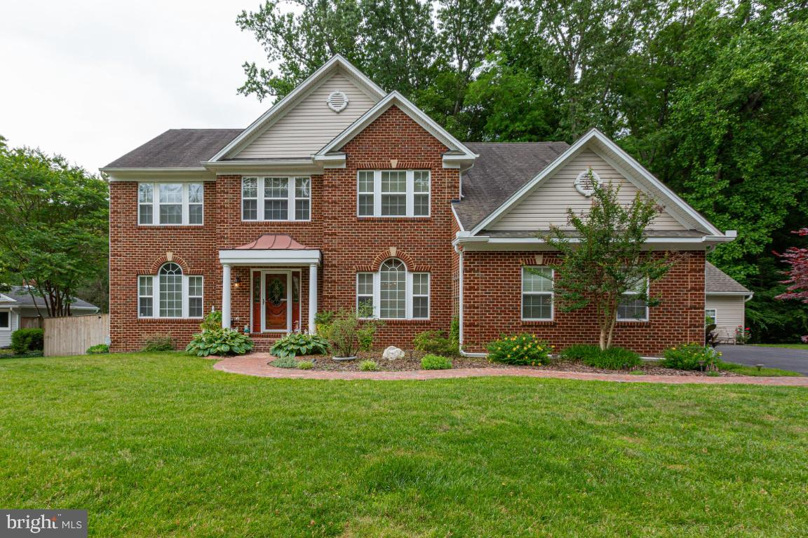No need to wait for new construction! This 5500+ fin sq ft custom built brick front colonial sts on 1.71 acres has it ALL.  When I say that this is a move in property that has it all, it is an understatement. Nothing to do but move in and place your furniture.  This one is a 10 and you'll be glad that it is priced to move and that you found it!  Located in the heart of Bowie, a stone's throw from routes 301, 50, 450 and 3, this is an entertainer's paradise.    Rock the music throughout using the in-house and deck speakers, attach to the surround sound in the family room and enjoy the fireplace, sit in the theater area in the basement and watch a movie and get goodies from the wet bar, sit on the deck or one of two patios and enjoy the lushly landscaped yard and BBQ, sit in the screened gazebo and eat crabs, cook in your gourmet kitchen w/oversized island,  enjoy your master suite w/vaulted ceiling, sitting room and 4 piece bath.  Three secondary bedrooms and a bath round off the upper level along with the oversized laundry room.  Work from home in your main level office, have company or au pair stay in their own suite in the lower level w/full bath.  The main level foyer opens into the living and dining room w/crown molding.   A 16x25 ft. morning room with skylights leads to the deck and patios in the rear yard.   Need project space? No worries, use the attached workshop.  The upper two levels and stairs have hardwood throughout.  The in-ground sprinkler system keeps the landscaping lush throughout. Close to shopping, Fine touches throughout including brick walkway and stoop and more.  Close to restaurants, Bowie Town Center, Crofton, AA County, Andrews AFB, DC, Baltimore and more.  This majestic colonial sits on 1.71 acres with a 4 car attached garage (2 car oversized garage) and a  10x25 sq ft. workshop attached.   The super extended driveway fits 8 cars.  Instant savings with NO Hoa fee, NO deferred water and NO sewer fee!  To top it off, the whole house generato