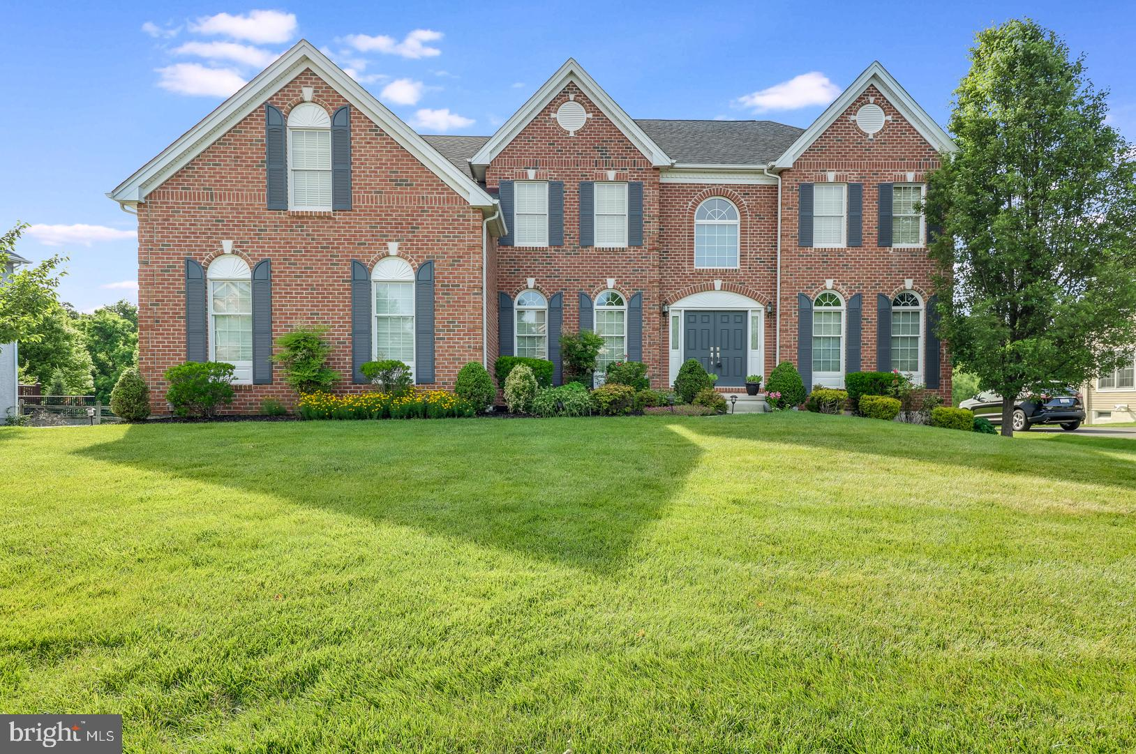 This stunning 4BR/4.1BA 6,100 square foot center hall colonial boasts virtually every Toll Bros upgrade imaginable! Sitting on a premium .46-acre lot and backing to open space and a wooded area on the quiet back side of the neighborhood, this spectacular house will check all the boxes. The moment you walk through the front door, you'll appreciate how much the owner has loved and cared for the home. The spacious 2-story center hall with custom woodwork and chandelier and eye-catching turned staircase is flanked by an elegant dining room with tray ceiling and chandelier and a formal living room with arched entries and floor to ceiling arched windows. Follow the upgraded hardwood floors into the breathtaking 2-story family room with vaulted ceiling and raised-hearth brick fireplace; massive office with double doors; spacious gourmet kitchen with granite countertops, huge center island,  pantry, and cabinets galore; and sunroom addition with vaulted ceiling and French door leading to oversized, maintenance-free, elevated composite deck. Head upstairs to the huge master bedroom with a walk-in closet that will make your knees weak and a five-piece en suite featuring a jetted soaking tub with waterfall spigot, his and hers vanities, tiled shower stall, and a large linen closet. The princess suite with private full bath and two additional bedrooms separated by a Jack & Jill bathroom round out the second floor. Head downstairs to the massive French door walk-out finished basement that has its own heating/cooling zone, tons of recessed lights, a full tile bathroom, and two separate finished rooms that could be used as a fitness room and additional office space.