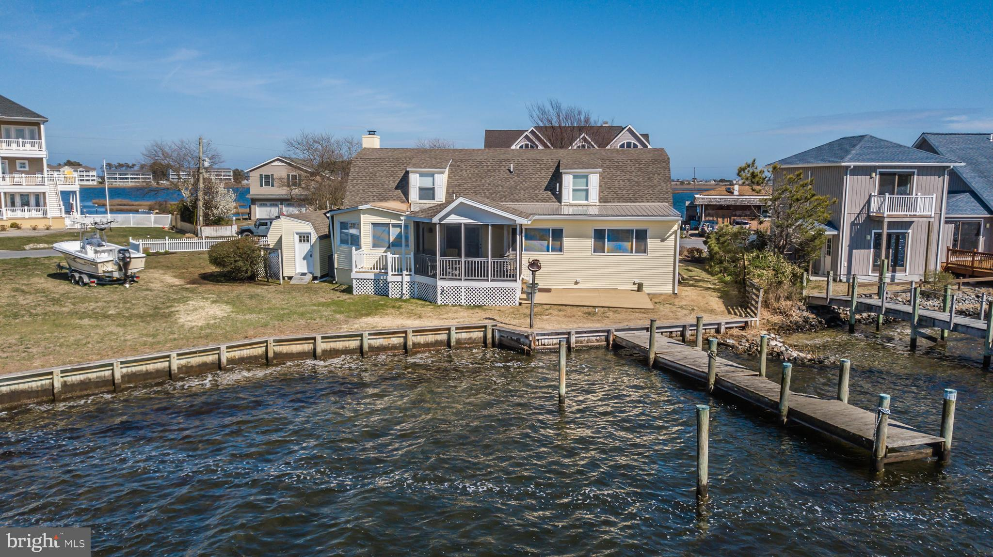 Bayfront! Beautiful Bayfront 4-bedroom, 4 bath home with expansive views over the bay. This newly renovated (2018-2019) home features living room with fireplace, kitchen with granite counter tops, stainless steel appliances, island and adjoining dining room that leads to the Bayfront all-season sunroom/family room with more area to dine. Includes screened-in porch and deck all overlooking the bay. Massive first floor master suite with a lovely tiled bath & double sink vanity. Guest bedrooms include one on the first floor and two en suite on the second level. Plenty of storage with garage style shed, backyard with private boat pier for boating, crabbing, fishing and just 2.5 miles to Fenwick & Ocean City Beaches