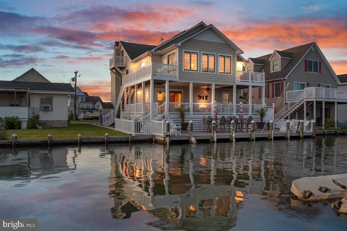 Sometimes words just aren't enough to really tell the story behind how impressive a property is.   This might be one of those times.   This house is two blocks west of the Rt 54 bridge, an easy bike or quick ride to both Ocean City and Fenwick Island.    Enjoy expansive and panoramic views of the bay and a breathtaking skyline from any one of your four private balconies, or the expansive dock/deck area!   Luxury vinyl/composite decking everywhere outside, and highlighted by a walk-in outdoor hot-water shower, to rinse off after a day at the beach, or on the bay.    Bring the whole family and spread out in this spacious 6 bedroom home, featuring a 1st floor owners-suite (including a kitchenette and walk-out to the ground-floor deck).   The second floor of this home is all original wood and beam ceilings, walls and hardwood floors, complimented by a glorious gourmet all-white kitchen (cabinets, quartz counters and backsplash), and offset with Bosch stainless steel appliances.     On this floor you can also enjoy three roomy bedrooms, a private dining room, waterfront sunroom, and a beautiful family room with 2-story cathedral ceilings.      Walk up an impeccably maintained all-hardwood staircase to the 3rd floor suite, with cottage-style bedroom, full bath and additional laundry room.