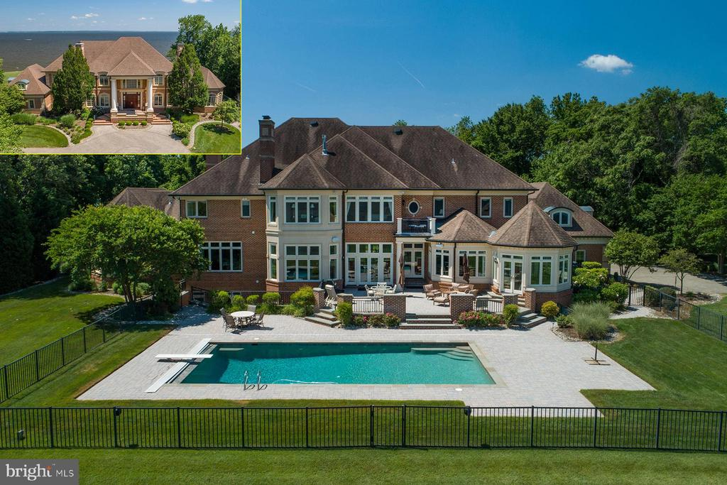 Absolutely stunning and meticulously maintained brick home situated on a 2+ acre waterfront lot with expansive views across the Chesapeake Bay. The unique and very private setting, with its' spectacular approach, only hints at the grandeur of this magnificent manor home.  The outdoor living space is great for enjoying the waterfront lifestyle with a heated in-ground pool, extensive hardscaping, and a level waterside yard. Bodkin Pointe offers a marina with deep-water slips, beach, and tennis courts; all are a short walking distance away.  As you step into the grand two-story foyer with marble floors and gorgeous, curved double staircase, you are immediately impressed by the intricate detailing that is present throughout the home. Noted builder Guy Pilli managed the construction of this 12,000+ square foot home and his level of precise implementation is evident. The custom painting, crown molding, and architectural details are just a few of the visually pleasing particulars found here. The foyer is flanked by a formal living room with hardwood floors and gas fireplace with marble surround; and, to the left, you'll find  the formal dining room also with hardwood floors and gas fireplace with marble surround. Through the dining room is a large butler's pantry that leads to the gourmet chef's kitchen. Sure to please even the pickiest of cooks, the kitchen leaves nothing to the imagination. Granite countertops adorn the breakfast bar, center island, and built-in prep space.  The top-of-the line appliances include 4-burner gas Dacor cooktop with griddle and downdraft, a Sub-Zero refrigerator, two wall ovens, two dishwashers, and a built-in microwave.  There is an informal dining space with huge water views, a built-in china cabinet, tray ceiling, and French doors that open to a four-season sunroom.  Adjacent to the dining space is a wet bar galley with prep sink and fridge that opens to the great room.  This space is truly magnificent with a stone wall, gas fireplace with