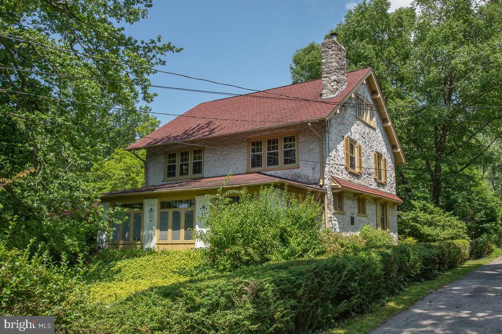 1915 architectural gem!    Walk to everything from this North Ardmore classic, well maintained stone Colonial.  Authentic millwork, deep windowsills, built-in bookshelves and French doors.  Great floor plan, good-sized rooms, hardwood floors throughout.  A handsome enclosed front porch greets you with detailed craftsmanship including Pella windows, window seats and lots of storage.  The living room is a feast for the eyes with three sets of French doors and a gorgeous fireplace hearth flanked by built-in bookcases.  Open to the living room is the dining room featuring a built-in corner cabinet.  From the living room you pass through French doors to the cozy, spacious den.  The mid-century styled eat-in kitchen is off the dining room. It features two ovens, a peninsula with sink and generous cabinet and counter space.  The kitchen opens to a bucolic back porch where you find yourself sitting in the middle of a mature, beautiful shady garden.  Also conveniently off the kitchen is the first-floor laundry room.  A powder room and center hall stairway complete the first floor.   The second floor has a center hallway from which you access the master bedroom, a second bedroom, and what is now being used as a home office.  There is a large bathroom with 2 sinks and vanities, a private water closet and private tub/shower area.  Ample storage.  The third floor has two more bedrooms, an additional bonus room, and an updated hall bathroom.  Exceptional walkability, steps from Suburban Square with Trader Joes, the Ardmore Farmers Market, and the Apple Store.   A 10 minute walk to the Ardmore train station with both local and Amtrak trains.  CHOICE of two award-winning high schools ~ Harriton HS or Lower Merion HS, which is a block away.   A whole house generator is included.