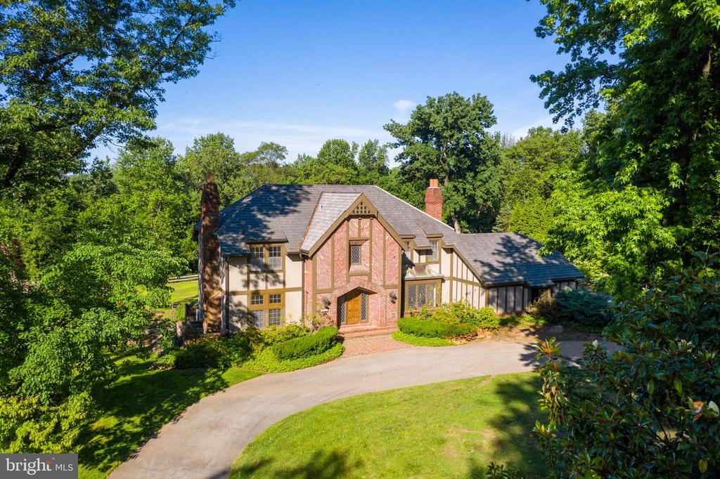 Ideally positioned on nearly an acre in one of the most desirable parts of the town, this elegant Tudor gem in the heart of Gladwyne is a must-see for buyers looking for a quiet, exclusive residence in a premier Main Line neighborhood! Set back on a tranquil, mature lot rests this remarkable 4 bed 5 bath family estate boasting an English flair, adorned with gorgeous herringbone brick cladding, lattice windows and a prominent arched entrance. Owners recently upgraded this gorgeous estate with major improvements, including: a public sewer hook-up, the installation of a gas line, a new heating system, a new hot water heater, newly cleaned vents, freshly painted interior, new sliding doors, and expensive old growth tree removal. The home has been virtually staged to highlight its superior appointments. The property affords dramatic interiors built to entertain, coupled by a serene park-like setting outdoors. Step through the cathedral-style front door to find a soaring light-filled foyer marked by a hand-honed, gently curved stairway that greets you upon entry. Generously proportioned rooms are all richly appointed and lovingly maintained, featuring detailed millwork, custom built-ins, and oversized windows bringing the nature in. In the handsome library, pegged oak floors, solid milled red oak walls, crown molding and wainscoting are complemented by a brick wood-burning fireplace, creating an enchanting space to unwind. For a more formal affair, head to the elegant dining room, which comes wrapped in oak crown molding and a tray ceiling ~ truly a space where memories are made!The grand parlor with raised flooring heightens the appeal, along with the gracious kitchen with Sub-Zero appliances, elongated peninsula, and ample pantries and closet storage. A warm and inviting family room adorned with chestnut built-ins steals the show, offering a vaulted ceiling and walls of picture windows overlooking the private grounds while bathing the room in natural light. The whole family will love the lower level den, media room, and game room which has convenient access outdoors. A private study, laundry room, and portico that leads to a fully-finished collector~s garage seals the deal. And there is plenty of space to host family and friends in comfort, with spacious guest bedrooms upstairs. After a long day, owners will appreciate the sophisticated master suite with a luxurious marble bath with step-up shower and soaking tub for the ultimate retreat. However, nothing compares to the secluded outdoor oasis! New sliding glass doors just off throughout reveal an expansive open backyard with a sparkling pool surrounded by new landscaping for maximum sunlight and aesthetic beauty. Living here also means being just steps from Philadelphia Country Club, and all the amenities of affluent Gladwyne, including top-ranked schools, restaurants, shops, and museums.