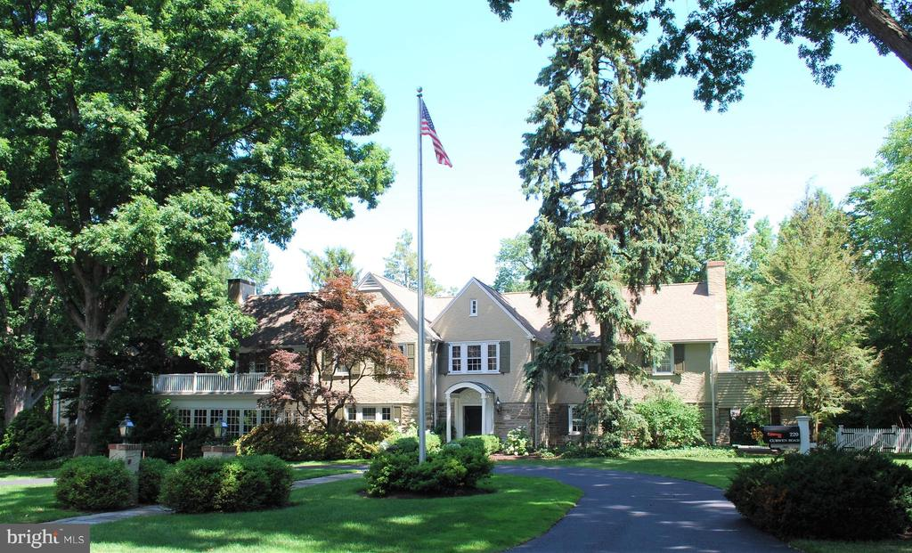 This elegant Colonial built in 1925 sits on a beautiful one-acre lot on a highly sought after street between Rosemont College and Villanova University.  The house is a comfortable 5,912 square feet, with 5 bedrooms, 5 full bathrooms and two 1/2 baths and is very family friendly.  The home has a magnificent center entry hall with wainscoting and French doors that lead out to the large stone patio perfect for entertaining. Off the front hall to the right is a large living room with a gas fireplace. Left of the center hall is a grand dining room that leads to an original butler pantry/wet bar area and the custom kitchen.  A centrally located family room/office area is adjacent to the dining room and has a step down to a cozy seating area with a gas fireplace.  A recently renovated kitchen with high end appliances, custom white cabinets and marble counters is conveniently located next to a bright and cheerful casual dining/sitting area.  Renovations to the second floor include a fantastic master bedroom suite with a comfortable sitting area with a gas fireplace and a custom dressing area.  Bedroom 2 has an attractive fireplace and an updated en suite bathroom.  Bedrooms 3 and 4  share an updated Jack and Jill bathroom and take advantage of a convenient back stairway that leads to the kitchen.  The large 5th bedroom has its own hall bathroom.  There is a partially finished lower level with a recreation area, a full bathroom and a custom 500 bottle temperature controlled wine cellar.  At the rear of the main driveway, a large covered carport leads to the back door and a convenient mudroom area.  Off the mudroom is a large family room with a half bathroom.  The fenced back yard features a hot tub on the patio level with a peaceful waterfall cascading into a gorgeous saltwater pool.  A beautifully landscaped yard with an irrigation system surrounds the pool and creates a remarkable private outdoor living space for family and entertaining.