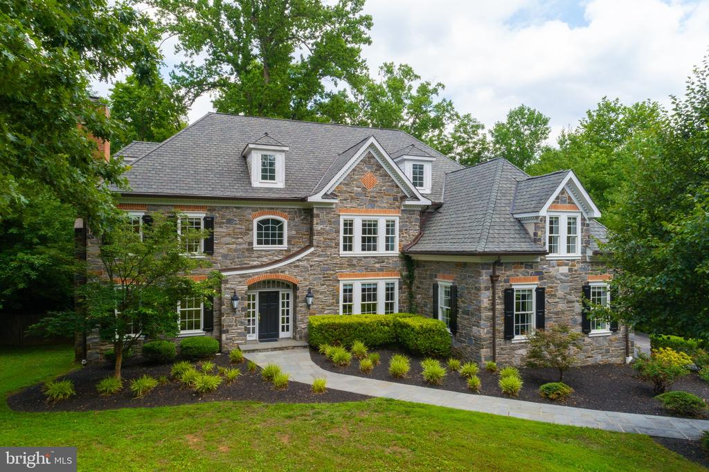 """This gorgeous, 5 bedroom, 5.2 bathroom, stone colonial is situated on nearly an acre of beautifully landscaped grounds and offers optimal privacy and serenity. Enter through a secure, gated entry and follow the private driveway shared with just one other grand home. This exquisite home is set far back from the road and is surrounded by lush greenery and fully fenced in grounds. A beautiful flagstone walkway will lead you to the inviting main entrance which opens up into an impressive 2-story foyer featuring a sweeping Juliette staircase, stunning architectural details, beautiful moldings, and rich hardwood flooring. This home's desirable open floor plan offers large rooms, high ceilings and ample natural light. The first floor houses a formal living room, formal dining room, family room, library, kitchen with breakfast room, two powder rooms and a mudroom, all which flow nicely into the entryway of the home. The large dining room with convenient access to a butler pantry features elegant chair rail detail and a beautifully designed triple window providing gorgeous views of the lush grounds. The spacious formal living room with gas fireplace leads to a formal powder room and elegant library with expansive built-in bookshelves and cabinetry. Adjacent is a large family room with vaulted ceilings, skylights, gas operated fireplace, custom built-ins, and french doors which provide access to a spacious deck and large, flat backyard. Off of the family room is an open-concept kitchen and breakfast room which offers both beauty and functionality. The gourmet chef's kitchen features granite countertops, tumbled stone backsplash, a large center island, 42"""" high cabinets, gorgeous custom-built armoires with Mackenzie Childs hardware, Miele coffee bar, Bosch Dishwasher, Viking oven and 6 burner gas range with grill and griddle, Viking hood and Viking refrigerator and GE microwave. The kitchen opens up to the butlers pantry and dining room making the first floor ideal for enterta"""