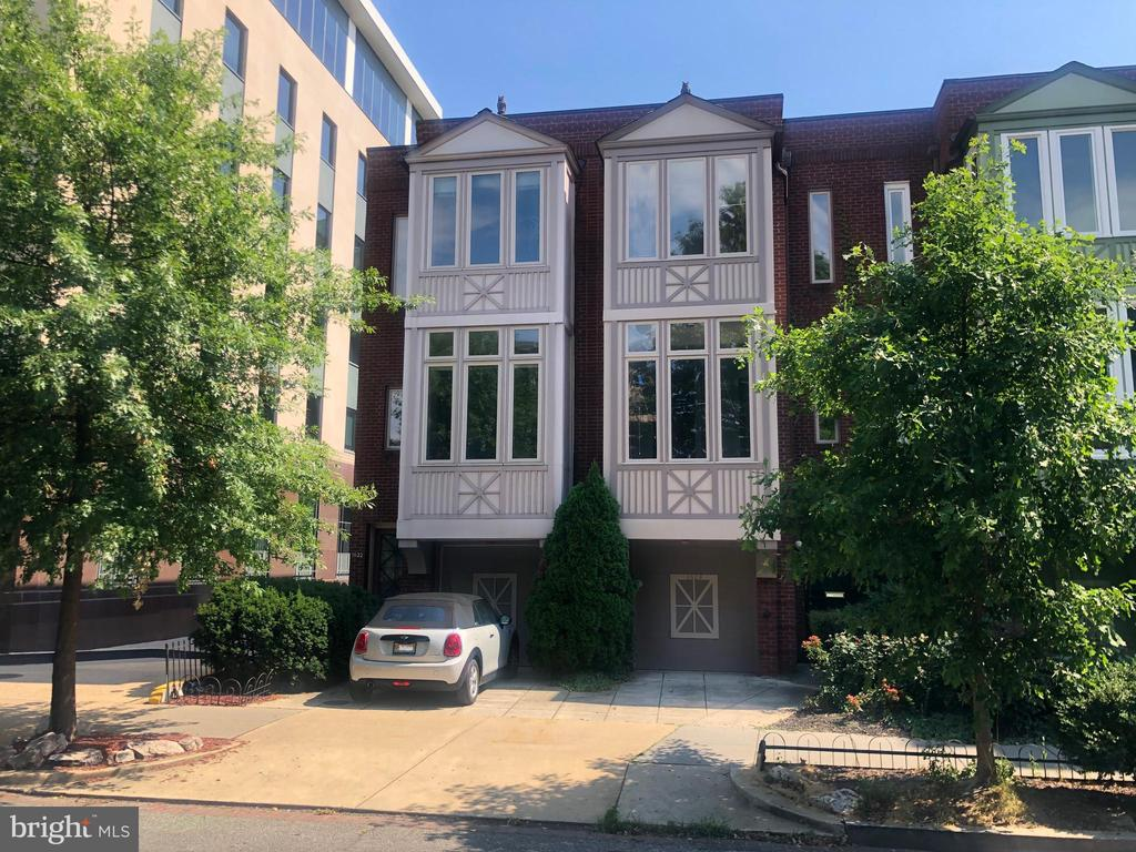 This unique end-unit townhouse offers a prime Dupont Circle location, airy ceiling heights, garage parking and access to everybody's favorite feature, a swimming pool right out back! You'll enjoy 2,408 square feet across three levels, with two bedrooms, 3.5 baths, a daylight walk out family room, private deck with steps to the garden and fenced rear yard. Gleaming hardwood floors, an open floor plan, 2 fireplaces, window bays and sunny kitchen with breakfast area are among the features. Stairs lead up to the main sleeping quarters, including a master bedroom with en suite bath and an oversized second bedroom with delightful bay and its own bath. The residence sits across the street from Stead Park and just two blocks from the famed Circle with its marble fountain. Walk to Whole Foods, restaurants galore and the Dupont Metro. It's the perfect opportunity to live in Washington's quintessential in-town residential neighborhood!