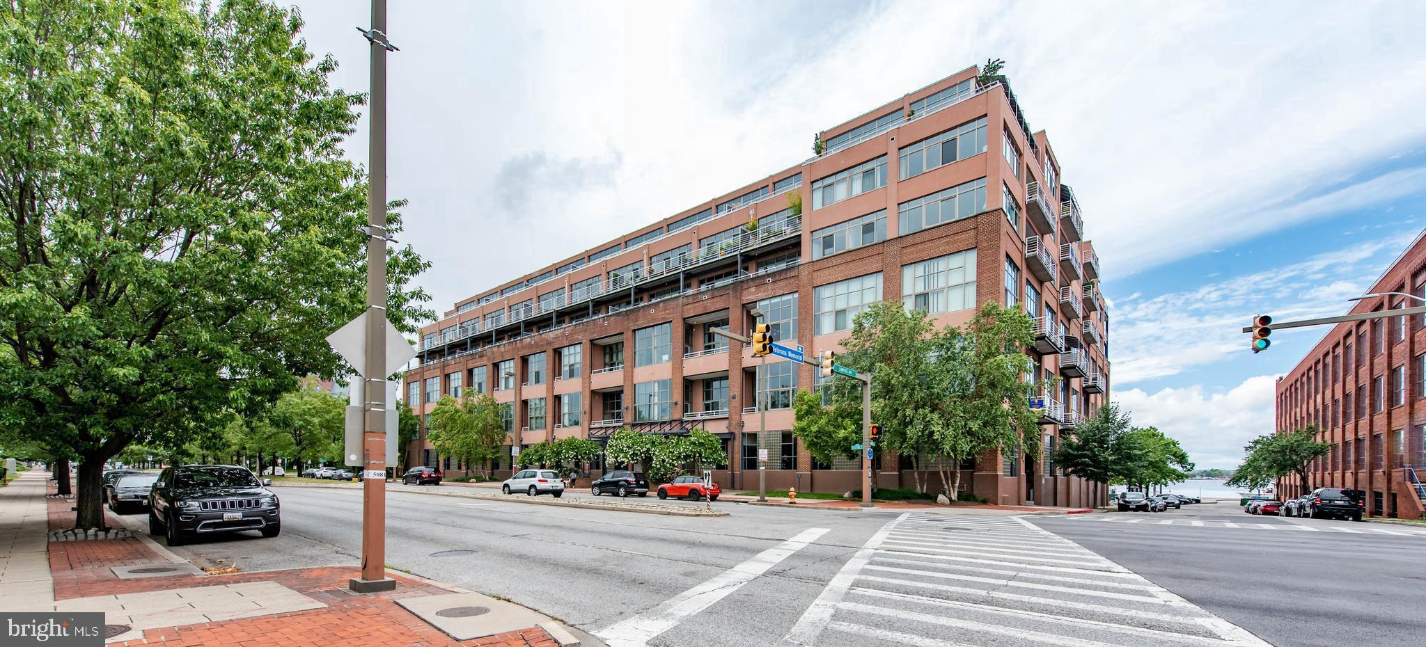 Stunning condo located in coveted Canton Cove on the waterfront featuring panoramic cityscape views. Floor to ceiling window, 9ft ceilings, wall to wall windows and covered balcony that stretches the length of the unit!  This home offers 3 bedrooms, each with balcony access, and 2.5 baths, including the Owner's suite with gas fireplace, custom walk-in closet, and deluxe full bath with marble tile, dual rain head shower, jetted tub and bidet. Beautifully updated kitchen features marble counters, island, black and stainless steel appliances and classic white cabinets.  Elegant formal dining room leads to a sundrenched living room boasting a cozy wood fireplace and a wall of windows with access to balcony.  Enjoy rooftop access for fireworks and parties, 2 assigned parking spots in private lot.   Stroll the Canton waterfront and visit the shops and restaurants in and around the square  as well as nearby Fells Point and Harbor East.
