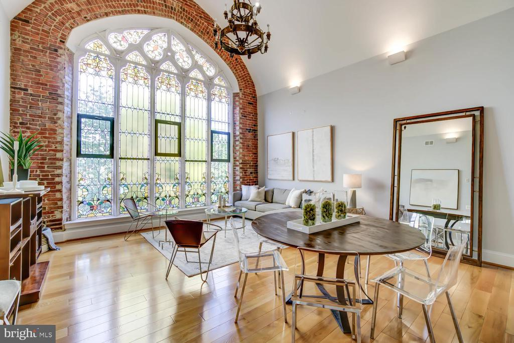 Welcome to The Sanctuary. Located in the Stanton Park neighborhood of prestigious Capitol Hill, The Sanctuary is a collection of 30 distinctive homes within the original 19th-century Gothic Revival church. Renovated in 2016, this dramatic two-level penthouse 2 bedroom and 2.5 bath city residence boasts a dramatic and luminous living space and includes a private parking spot. This rare offering includes a breathtaking floor to ceiling stained glass window that has been exquisitely restored and serves as the centerpiece of the spectacular entertaining space. Other features include an original chandelier, 20 ft ceiling, exposed brick walls and wide plank hardwood flooring throughout. Chefs will love the well-equipped kitchen with a JennAir gas range, Zephyr range hood, KitchenAid stainless steel refrigerator and dishwasher, breakfast bar, and imported Italian stone countertops. First-floor owner's suite with stained glass windows, en suite marble bath, and two closets. The second-floor guest bedroom features a cupola skylight and an open loft floor plan overlooking the first-floor living space. The second-floor guest room also includes an en suite bath and oversized closet. The first floor includes a powder room, laundry room,  and a whole-home water purification system. Bicycle storage on-site | Elevator | Professionally managed | Pet friendly | One assigned parking space.  The Sanctuary is in the heart of vibrant retail, restaurant, and nightlife scene bounded by Pennsylvania Avenue, H Street, and Barracks Row, and is walking distance to Whole Foods and Trader Joes. Close proximity to Capitol Hill,  Eastern Market, Stanton Park, and nearby Metro stations (Union Station and Eastern Market).