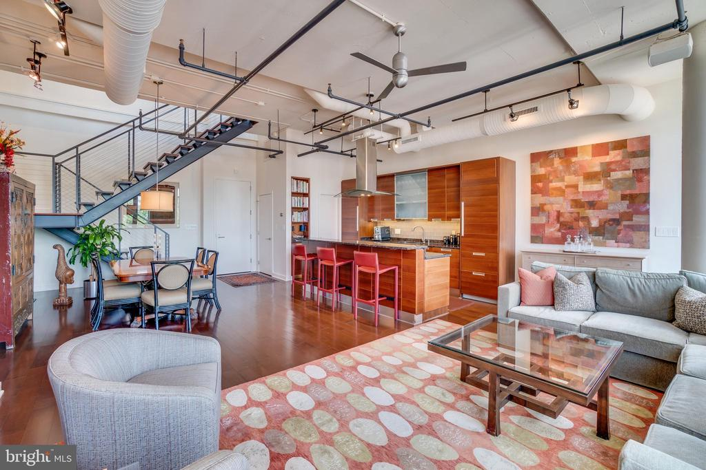 This one of a kind, duplex penthouse at historic Lofts14, formerly an early 1900~s auto repair, is one of only a handful of true loft condominium buildings in Washington, DC. This unique home was designed by the current original owner in conjunction with the builder and architect to combine two units into one stunning 2,005 SF duplex loft Penthouse.The unit is flooded with light from a wall of floor to ceiling windows and there are French doors leading to a generously sized Juliet balcony. The living room, dining area, and kitchen are all situated in perfect harmony, each with plenty of space, making them feel like totally separate rooms. The living room has copious amounts of storage thanks to the built in shelves and drawers, all meticulously designed around a gas-log fireplace. The kitchen features Scavolini cabinetry, reminiscent of paneling on a yacht, separate SubZero refrigerator, and freezer, Miele dishwasher, stainless steel drop in 5-burner gas range, wall oven, hidden under-counter microwave, floating glass and stainless steel hood vent, gleaming granite countertops and a spacious pantry with abundant storage.On the main level, there are two bedrooms, each with abundant light and en-suite spa bathrooms. The main bedroom boasts a large spa bathroom with dual sinks, separate water closet room, an oversized shower with a built-in tv in the shower, and speakers throughout. The walk-in closet for two is by Closets by Design. The second bedroom, currently used as a guest room and office, has a custom built-in murphy bed and sleek window treatments. Just beyond the second bedroom, there is a full bathroom and a laundry room complete with built in cabinetry.Ascend the custom floating metal switchback staircase to yet another stunning outdoor view. The 510 SF second level is currently being used as an office, but the space would be ideal as a second living area or family room. The space offers guests a powder room, separate wet bar area with under counter fridge, discreet paneled Miele dishwasher, and Scavolini custom cabinets. Finally, step out through two sets of French doors to the totally private, 720+ SF professionally landscaped rooftop terrace where you will find unobstructed panoramic city views.