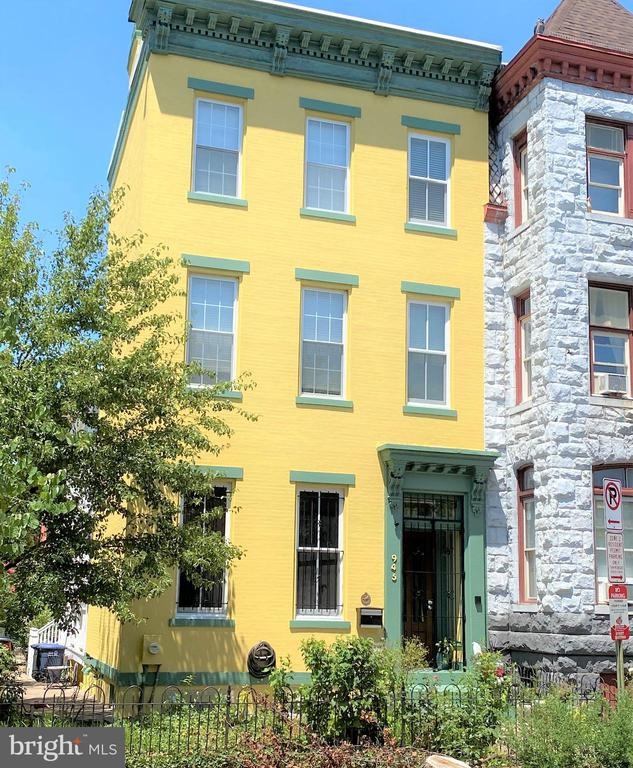 945 O Street, NW was constructed circa 1872 and was the most expensive house on the block at that time.  Now it is arguably the most charming and a jewel of this historic area.  In 1883 the double porches were added, making it inviting as well as handsome.  The current owners have made great use of the porches recently with the large, efficient ceiling fans.  Sunsets are easily enjoyed given the porch's west facing view.  The house has a rich history that parallels the story of the development of the District of Columbia and the Logan Circle neighborhood.  Expansive and stately, the house is suited for all kinds of entertaining as well as everyday living.  The parlor is stunning with nearly 12-foot ceilings and impressive ornate plaster moldings.  The gas fireplace adds to the charm of this exquisite room.  Another unique feature is the large shuttered window that looks out over the porch.  The dining room is well suited for large dinner parties.  That room also boasts a high tin ceiling and a beautiful decorative mantle.  Pass by the side door that leads to the porches and side yard and find a large kitchen is fitted with ample storage and modern appliances.  It is a kitchen designed and built to cook and entertain with its granite topped island providing food preparation space as well as casual dining opportunities.  The current owners were charmed by the kitchen's historic features of the (non-functioning) servant bells and the plate warmer radiator.  The side door leads to an enclosed courtyard with brick patio. The stairs lead to a split landing going to the bedrooms on the second floor.  The bedrooms are basically suites with each bedroom having a full bath adjacent.  The second floor has two of those bedrooms and office space.  There are custom closets, ample storage and a convenient laundry room.  The third floor makes a delightful secluded bedroom suite.  Among the other desirable features is a large storage basement containing a 500-bottle wine cellar.  A truly unique addition to the property is the two-story carriage house, originally a stable,  separated from the main house by that charming courtyard area.  The 900 sf carriage house is currently set up as fully functioning living space and was used as guest quarters by the current owners.  It has a full kitchen and laundry facilities.  That makes a total of 4 bedrooms and 4-1/2 baths.  There is off street parking for two cars.  945 O Street is superbly located with ample shopping, dining and recreation facilities nearby.  Trendy Naylor Court and Blagden Alley are the next two blocks south. A Walk Score of 96 demonstrates most errands can be accomplished locally.  All Metro line stations are located within blocks of the house.  Major bus lines and access roads make getting anywhere easy.  Those conveniences result in a Ride Score of 92.  While offering the magnificent look and feel of another century, 945 O Street has the critical updates that elevate it to today's living standards in an ideal setting.
