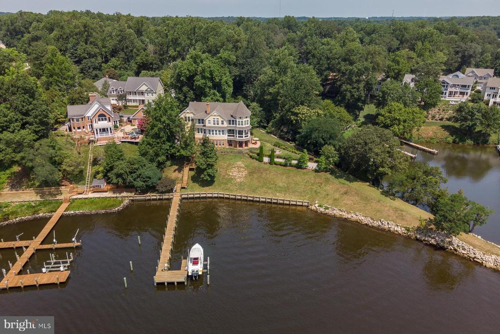The epitome of luxurious waterfront living awaits in this sensational custom-built residence. Timeless elegance, classic charm and a host of contemporary features combine with show-stopping views over South River to create a unique home that truly must be seen to be believed.From the prestigious cul-de-sac location to the striking curb appeal, landscaped gardens and grand double door entry, you will fall in love with this property even before stepping inside. The layout is set over 7,230sqft and boasts five bedrooms and 6.5 baths along with sprawling indoor and outdoor living spaces.This is a rare and highly sought-after opportunity to secure your own spectacular slice of South River waterfront.Gleaming wood floors and a stunning two-story entry welcome you inside while decorated ceilings, on-trend muted color tones and an abundance of natural light are on show throughout. Oversized windows perfectly frame views over the water from most rooms in the house including the spacious living room and the formal dining.The gourmet eat-in kitchen is ready and waiting for the avid cook, complete with sweeping Silestone countertops and a center island with breakfast bar seating. A suite of GE Monogram appliances will make preparing meals an absolute pleasure plus there~s a stunning tiled backsplash, gorgeous cabinetry, dual sinks and a generous walk-in pantry.Opulent and beautifully appointed, the master suite is your own private oasis with water views, a wet bar and dual custom walk-in closets. At the end of the day, you can retreat to the luxurious master bath with standalone tub and a walk-in shower along with a private water closet. The remaining second-floor bedrooms all have ensuites while the finished basement houses an additional bedroom and two full baths. There~s a well-equipped second-floor laundry room, plantation shutters and an attached garage plus the home is run on geothermal energy and has a backup whole-house generator.Two fireplaces guarantee a cozy ambience on cool winter nights while outside you can host friends on the screened porch and admire the breathtaking outlook, relax on the covered patio or gather around the custom-built fire pit. There~s also a private pier and an electric boat lift making it easy to enjoy a day out on the water.
