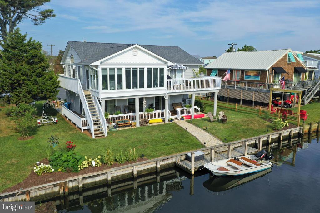 Beautiful canal front home with a private boat dock located just a few blocks to the life-guarded beach in South Bethany. This lovely coastal home features an inviting open floorplan with vaulted ceilings, large waterfront sunroom, gas fireplace, and beautiful kitchen with upgraded cabinetry, granite countertops, and stainless steel appliances. An additional family room on the first floor allows plenty of space for everyone to spread out. Excellent outdoor living space includes a large waterfront deck and a spacious covered porch overlooking the canal. Walk to the beach or spend the day on the bay with the convenience of docking your boat at your back door. Located on a quiet street with no thru traffic, this is the perfect beach retreat.