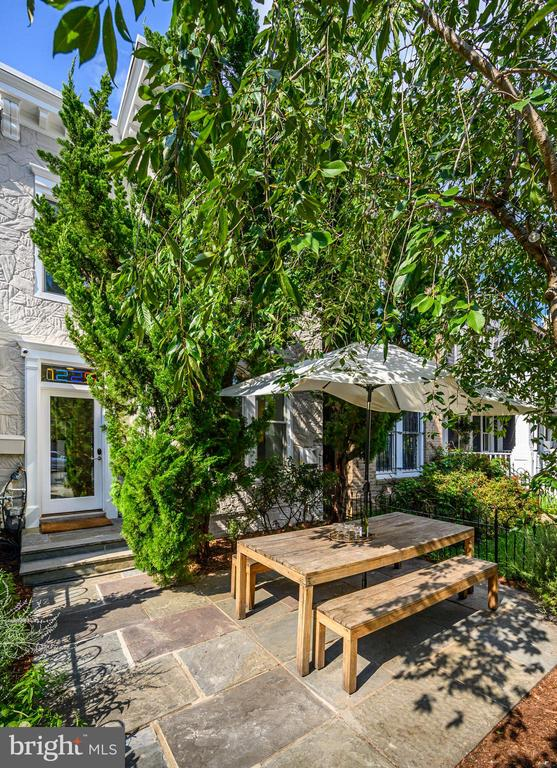 Welcome to 1225 S St. NW, at the intersection of modern luxury and sustainability. This eco-home greets you with the first of three beautiful outdoor spaces: a deep vegetable garden with herbs leading to a flagstone patio shaded and hidden by a magnificent and mature weeping cherry. Cross the threshold under the neon 1225 created by renowned artist Craig Kraft and into a surprisingly and smartly designed modern interior framed by a Victorian shell.    The main level features a true open floor plan, allowing light and cross ventilation, to reduce electric usage. The front houses a picture perfect seating area, with bay window seating shielded by the mature junipers. Fashionable under stair storage and a powder room lead you to the directly combined dining and living area, complete with reclaimed oak table and countertops, luxury appliances, a hidden pantry, and a custom art-gallery system to border it all. A bonus area continues the path to the second outdoor space, a brick patio with Dero bike racks, pegboard storage, a side garden with a maple tree, and room for a car.    Upstairs, you will find three bedrooms and two full bathrooms, with beautiful views to the outdoor spaces. The generous bedrooms are accented by the bright Fitzfelt closet doors and Elfa systems. Tiles in the elegant bathrooms are not marble, but recycled glass. The main suite is completed by a private deck, the perfect bucolic getaway in the heart of the city and overlooking DC history. Make this sustainable home yours, and help do your part for planet Earth, all while living luxuriously in Logan.  Inquire for more details of all the eco features, or to set up a private tour.