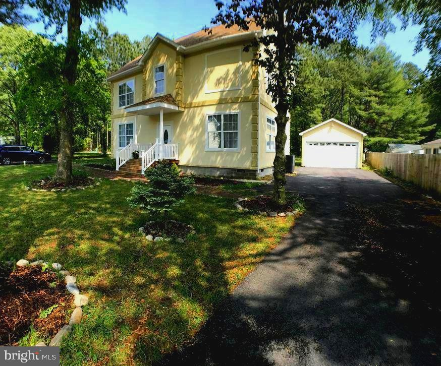 Price Reduced! Motivated Seller! Spacious home with 3 living levels located 3.7 miles from Bethany Beach Delaware. The first floor features an efficient floor plan with a living room that is filled with natural light, generous kitchen that opens to a separate dining area, guest bedroom, full tiled bathroom, and a separate laundry room. The backyard deck, surrounded by serene nature, includes ample seating that's ideal for outdoor entertaining. On the second level, you will find a primary owner's bedroom with a walk-in closet that has built-in shelving, sliding door that opens to a large balcony, en suite bath with a heated floor, jacuzzi tub, tiled shower with multiple shower heads, 2 additional bedrooms, and a full tiled hall bath. The third level offers more sleeping spaces along with a family room area. Enjoy the conditioned entertaining garage. This home sits on two lots with a long-paved driveway and a second paved pad for overflow parking. Additional features include a new hot water heater and well pump in 2019, vapor barrier in the crawlspace, 2 water softener systems, dual zoned HVAC systems, high voltage wall outlet in the garage, and a 400 amp electric panel.  The convenient location has no HOA fees and no city tax.