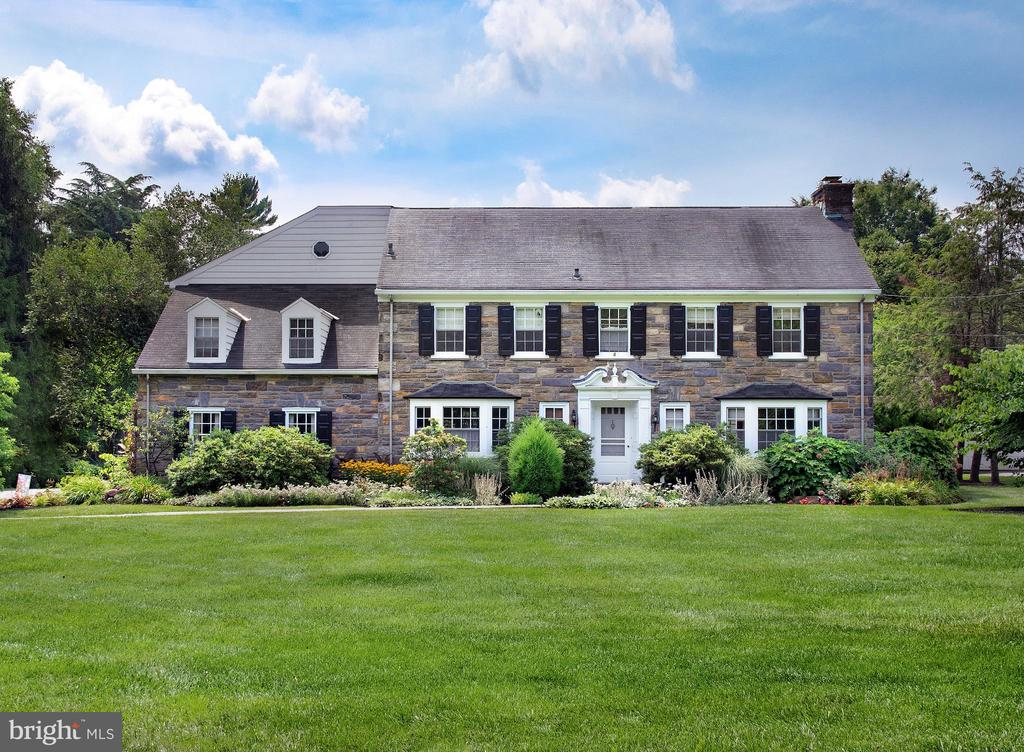 This finely-maintained Colonial in desirable Haverford has been so comfortable and well-loved, that the current owners have lived here for over 30 years! The spacious 5 bedroom 4.2 bath beauty is ready for you to call your own, so you can make lasting memories with your family in the best neighborhood on the Main Line. Set on 1.21 pristine manicured acres, this stately home has so many attractive features beginning with a stone façade, built-in heated 2-car garage, upper and lower decks, and bluestone patio overlooking picturesque rear grounds. A sprawling flat lawn where the kids can play sports and lush gardens, trees and shrubbery all around create a park-like setting, the real highlight of this special property. There's even an irrigated vegetable garden out back so you can grow your own produce. If a pool is on your wish list, lots of space exists for that summertime oasis you've dreamed of. Inside, generously-proportioned rooms and a gracious flow are perfect for entertaining and parties of any size. The elegant entry hall opens to a living room with fireplace and formal dining room for easy mingling. The heart of the home is the open kitchen, breakfast and family room where the most time with loved ones will be spent, cooking, eating and watching TV together. Sets of sliding doors open to the lower deck for lounging and outdoor dining. Escape to the quiet wood-paneled den with built-ins when you want to curl up with a good book or cup of coffee. On the 2nd floor is an enormous master bedroom wing, a true hideaway complete with an office, large spa-like bath with tiled shower, separate tub & double sinks, and access to the upper deck. 4 additional spacious bedrooms – 2 with en-suite baths – are perfect for family and guests. A laundry hookup exists on this level; plus a chute goes right to the basement laundry area. Also in the basement is a huge deep freezer from the 50's that still works great for additional food storage and tons of storage space. New to the