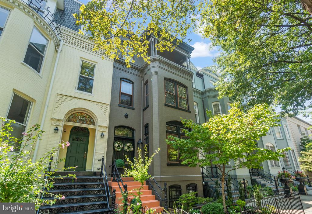 Located on the cusp of the Logan and Dupont Circle neighborhoods, this stunningly-renovated four-story, Bayfront Victorian showcases period details and luxurious appointments. Step through the original double-door entry to an inviting foyer, accented by inlaid herringbone white oak floors. The gracious living room has views of treelined P Street and features one of the six fireplaces. Take delight in beautiful natural wood trim, large windows with plantation shutters, and lovely hardwood floors throughout the home. A separate dining room offers a comfortable entertaining space for dinner parties, and the renovated kitchen will impress even the most experienced home chef. Outfitted with wood cabinetry and built-in appliances, it includes white quartz countertops, a stainless gas range, pantry, and a large island with bar seating. South facing kitchen windows fill this room with light and overlook the private rear deck - perfect for enjoying your morning coffee or sitting with friends for an evening cocktail. A main level powder room is adjacent to the grand staircase - an ornate showpiece of the home featuring custom millwork created by skilled craftsmen over a century ago. Ascend these stairs to the second level and retire to one of the two spacious bedrooms, each with a fireplace, that share a large bathroom with marble tile shower, dual washstands, and slate-toned flooring with penny tile accents. The laundry room with additional storage is located on this floor. The upper level of the house is dedicated to the private owner's suite, featuring an exposed brick wall, fireplace, and a balcony overlooking the treetops. Pass the custom walk-in closet to the en suite bathroom, complete with a marble walk-in shower with herringbone floor tile and a dual sink vanity with ample storage. Newly renovated, the lower level provides a splendid in-law suite accessible from the main level as well as its own front and rear entrances. This suite features new porcelain tile flooring, a thoughtfully designed kitchenette, its own washer and dryer, and a bedroom with a full bathroom. The home includes covered, two-car tandem parking as well as a third off-street surface spot. It is exactly one block from the Whole Foods Market, and provides immediate access to the 14th Street Corridor for shopping and dining, Dupont Metro station, and is minutes from downtown DC.