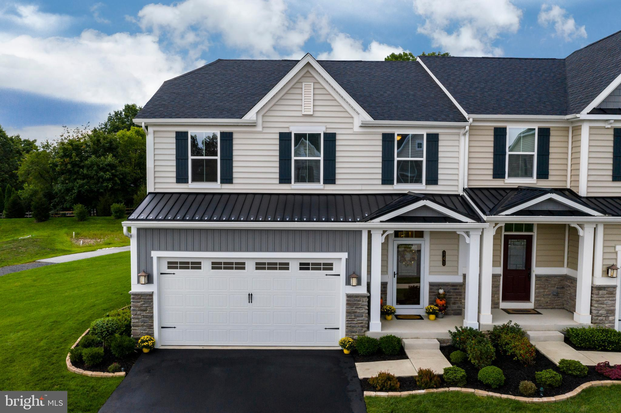 "Welcome home to this bright and beautiful Misthaven model in Collegeville's luxurious Highpointe at Providence community! This like-new carriage home has a prime location backing up to a tree line and walking trail, boasts a 2 car garage, and has incredible curb appeal with professional landscaping and thoughtful exterior finishings. From the moment you enter from the covered front porch, you can tell that the current owners have taken incredible care of this home to keep the new construction feel. A powder room and coat closet are conveniently located in the formal entryway with hand-scraped hardwood flooring that flows throughout the entire first level.  Large arched entryways, crown molding, and chair rails, lend a regal feel to the open floor plan. As you begin your tour, you come to a dining room with floor to ceiling built-ins (currently being used as a kids' playroom) and a large family room with recessed lighting and a peaceful backyard view. These rooms open to the gorgeous upgraded kitchen with granite countertops, range hood above the stove, a 4-seat custom butcher block island with pop-out microwave, beautiful ceiling-high subway backsplash to compliment the updated cabinet trim, huge single sink with goose-neck faucet, and a convenient walk-in pantry.  Just off of the kitchen is a spacious morning room with sliders to a new bluestone patio that has 2 seating walls for huge gatherings and a spot on the side for your grill! Upstairs you will find the large master suite with a walk-in closet with built-ins and a private bath with dual vanity, soaking tub, and stall shower. The second floor also has three additional right-sized bedrooms with closet built-ins and ceiling fans, a neutral full hall bath, a stunning laundry room with custom built-ins and utility sink, and upgraded carpet and padding throughout.  If you are looking for even more reasons to say ""yes"", there is an immaculate garage with epoxy floors and spray foam insulation, a whole house water softener and humidifier, an exterior drip irrigation system, a walking trail that connects between the neighboring communities, and a large side and back yard for your kids or four-legged friends. Conveniently located just minutes from Providence Town Center, Phoenixville, Oaks, King of Prussia, and all major highways, this home has it all! Schedule your showing today!"
